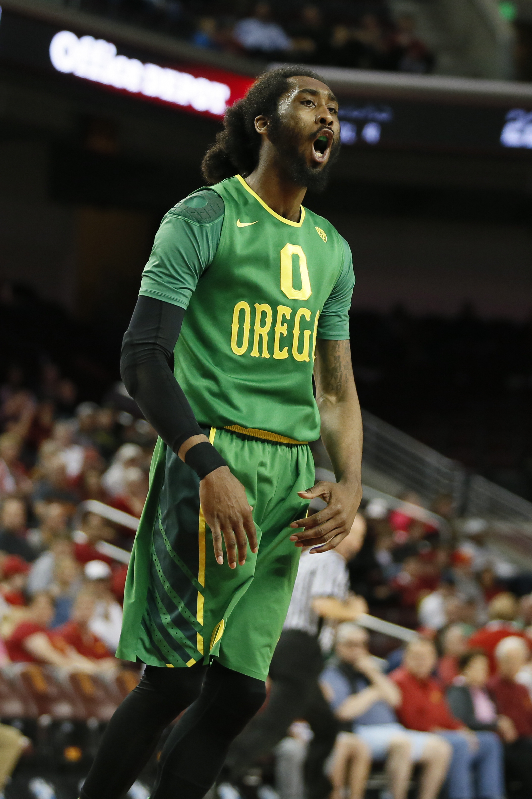 Oregon's Dwayne Benjamin celebrates after dunking the ball over Southern California's Chimezie Metu, not pictured, during the first half of an NCAA college basketball game, Saturday, March 5, 2016, in Los Angeles. (AP Photo/Danny Moloshok)