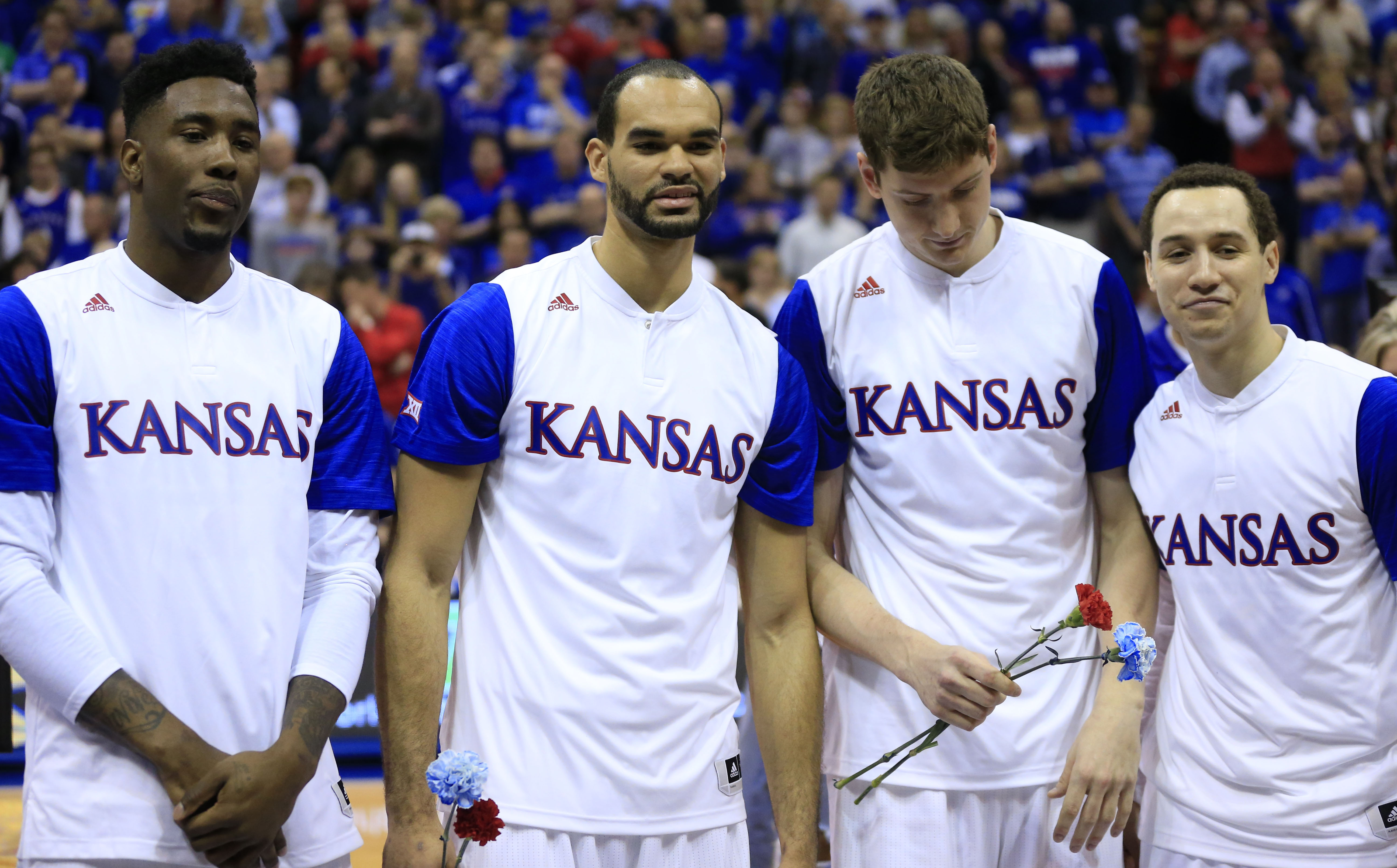 Kansas seniors, from left, Jamari Traylor, Perry Ellis, Hunter Mickelson and Evan Manning, right, pose for a photograph before an NCAA college basketball game against Iowa State in Lawrence, Kan., Saturday, March 5, 2016. (AP Photo/Orlin Wagner)