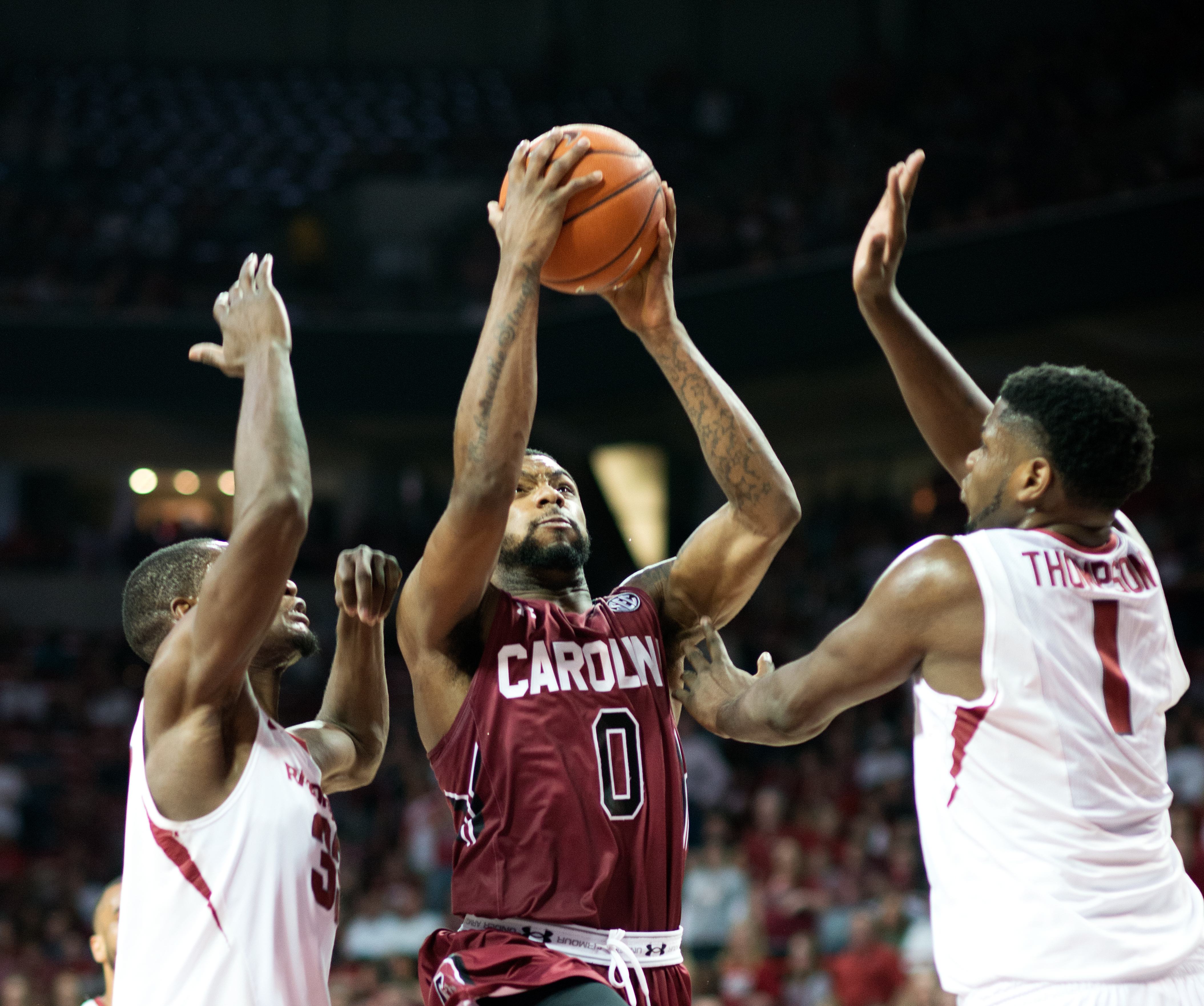 South Carolina's Sindarius Thornwell (0) shoots a basket over Arkansas' Moses Kingsley (33), left, and Trey Thompson (1), right, in the second half of an NCAA college basketball game in Fayetteville, Ark., Saturday, March 5, 2016. South Carolina won 76-61