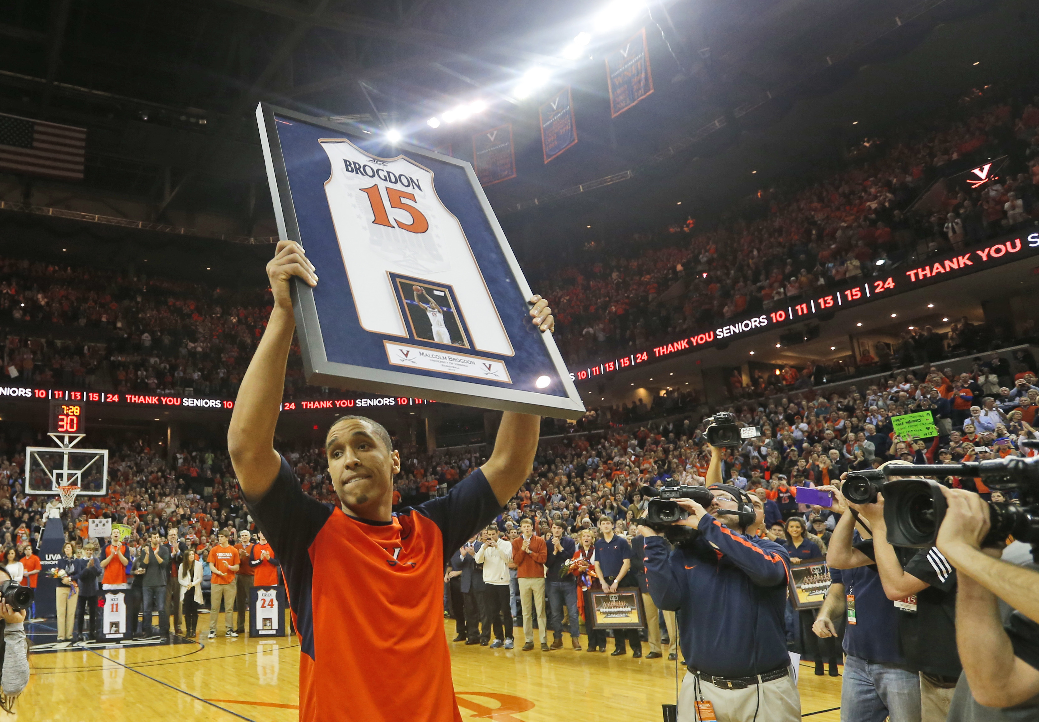 Virginia guard Malcolm Brogdon (15) holds a commemorative jersey as he is introduced prior to the team's NCAA college basketball game against Louisville in Charlottesville, Va., Saturday, March 5, 2016. Brogdon is a graduating senior. (AP Photo/Steve Helb