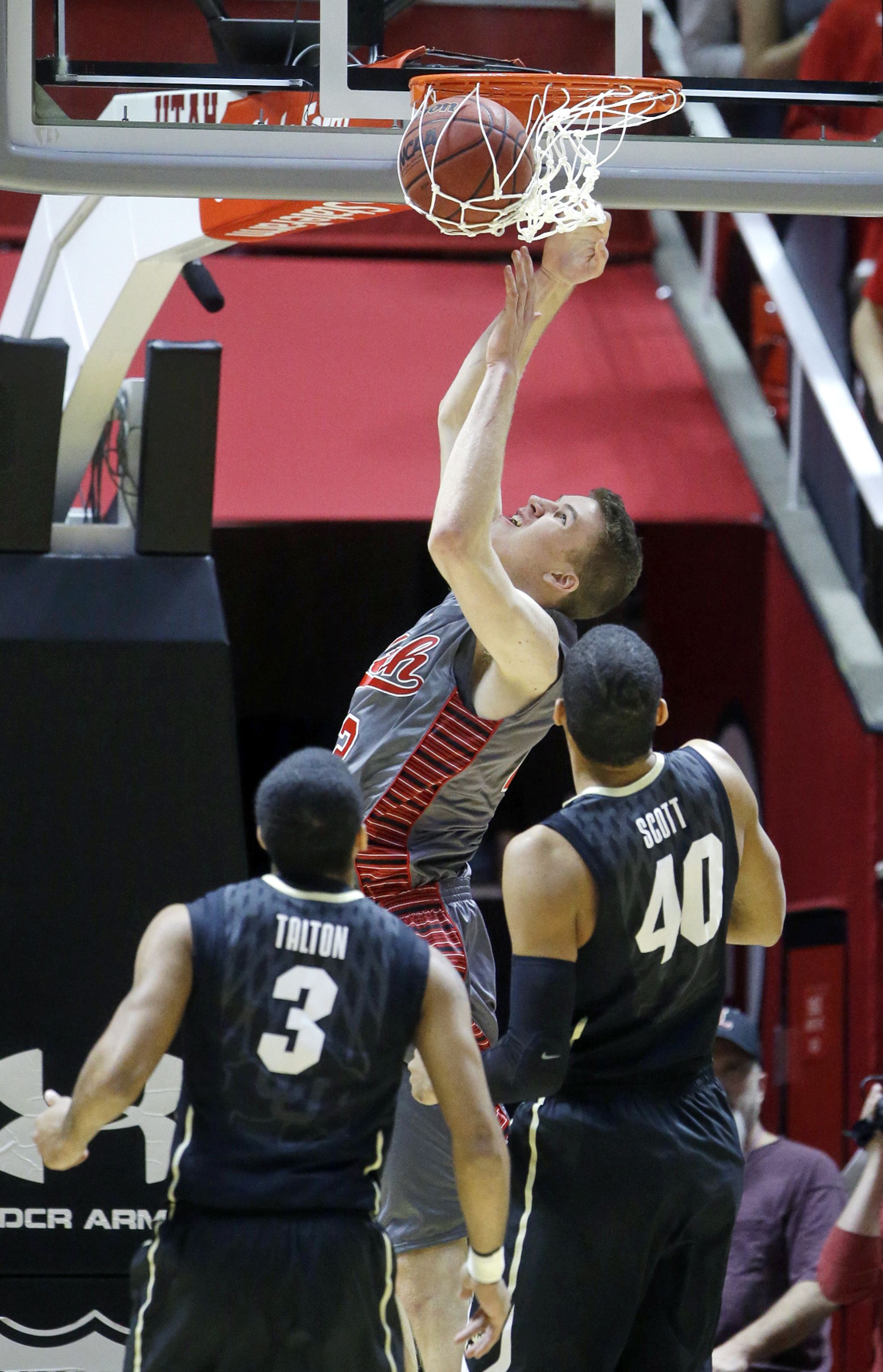 Utah forward Jakob Poeltl, top, dunks the ball as Colorado's Xavier Talton (3) and Josh Scott (40) look on during the first half in an NCAA basketball game Saturday, March 5, 2016, in Salt Lake City. (AP Photo/Rick Bowmer)