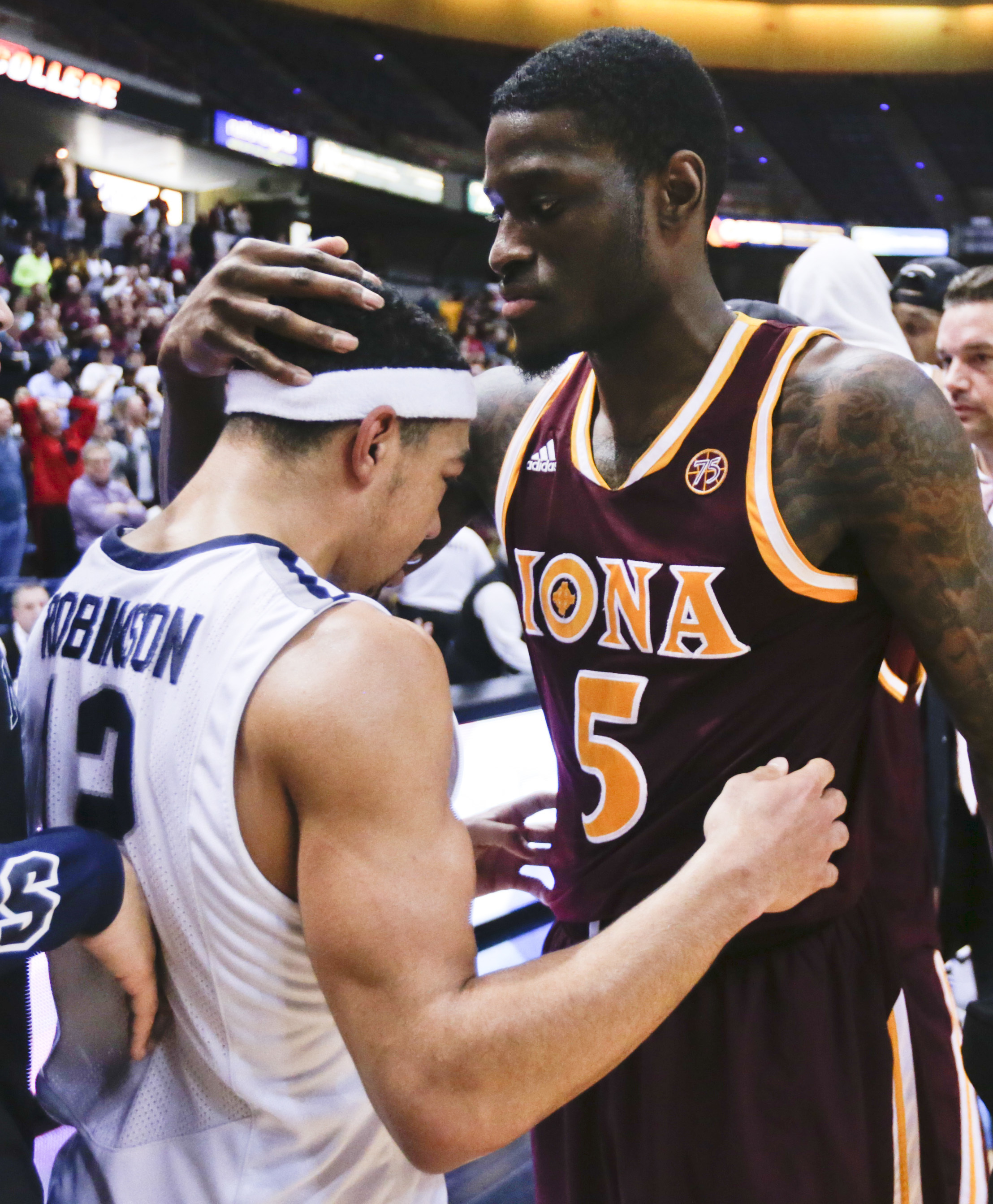 Iona guard A.J. English (5) embraces Monmouth guard Justin Robinson (12) after Iona's 79-76 win in an NCAA men's college basketball game in the championship of the Metro Atlantic Athletic Conference tournament on Monday, March 7, 2016, in Albany, N.Y. (AP