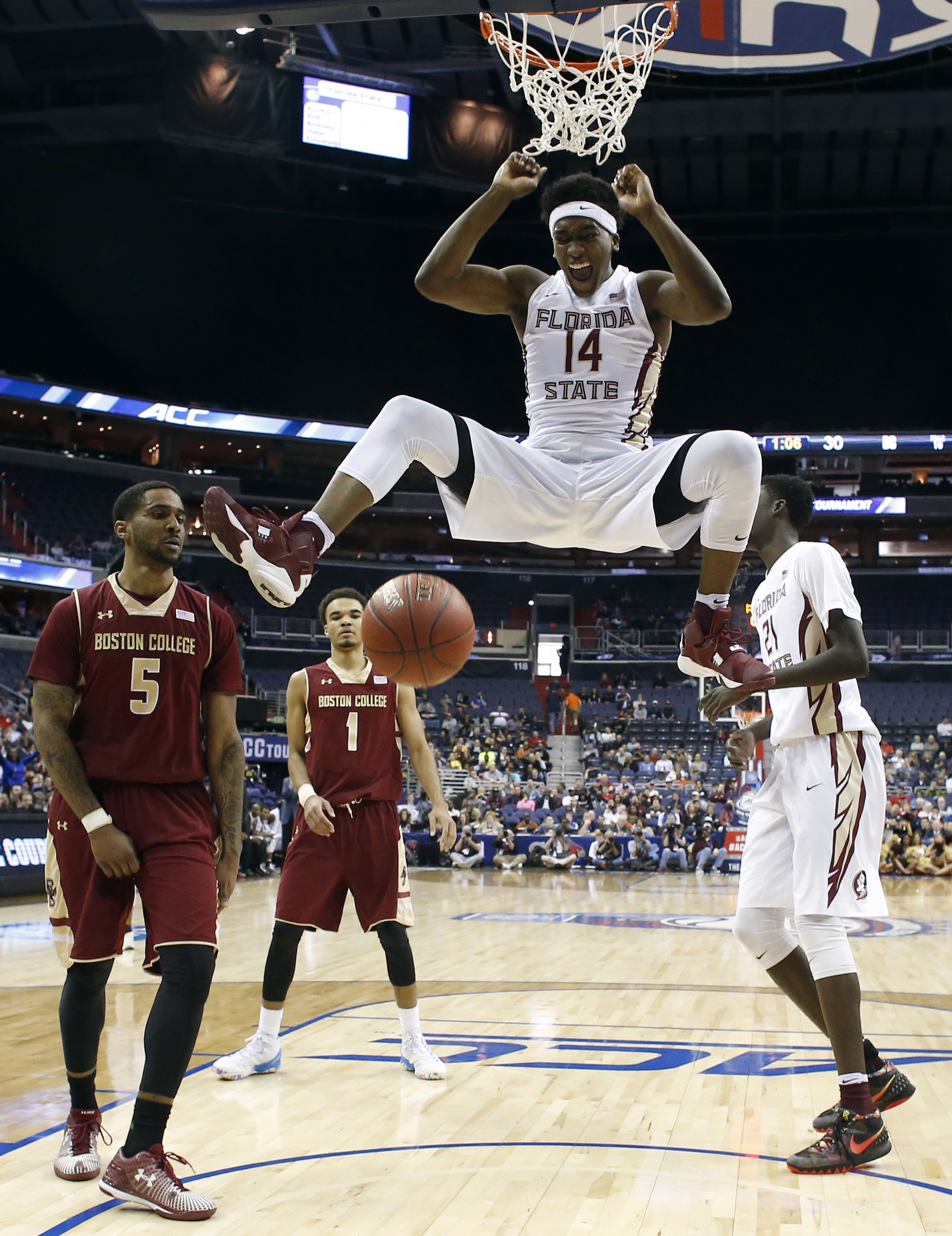 Florida State guard Terance Mann (14) reacts after dunking the ball in front of Boston College forward Garland Owens (5) and guard Jerome Robinson (1) during the first half of an NCAA college basketball game in the Atlantic Coast Conference tournament, Tu