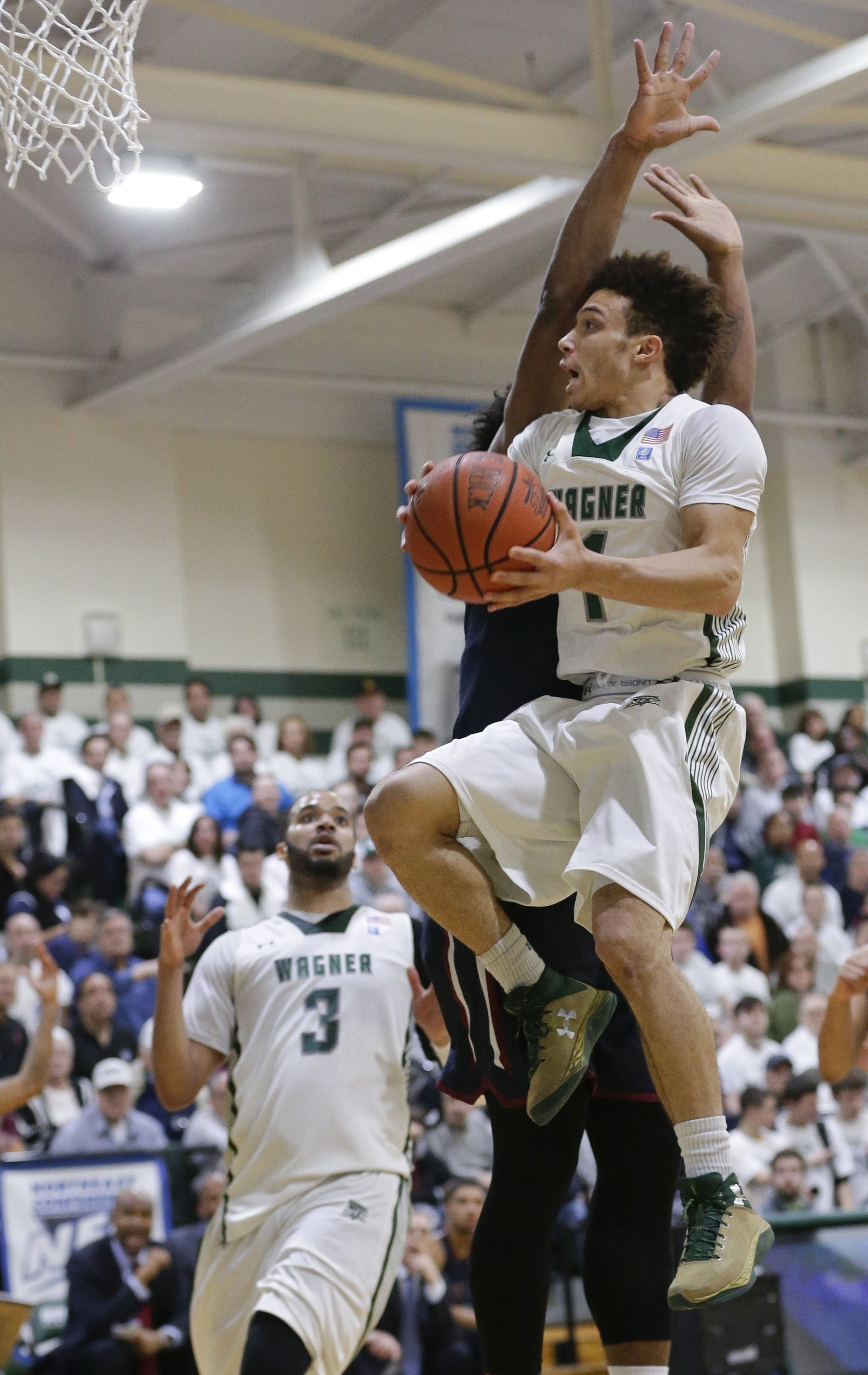 Wagner's Aaren Edmead (1) drives past Fairleigh Dickinson's Mike Holloway during the first half of an NCAA college basketball game in the championship of the Northeast Conference tournament, Tuesday, March 8, 2016, in New York. (AP Photo/Frank Franklin II