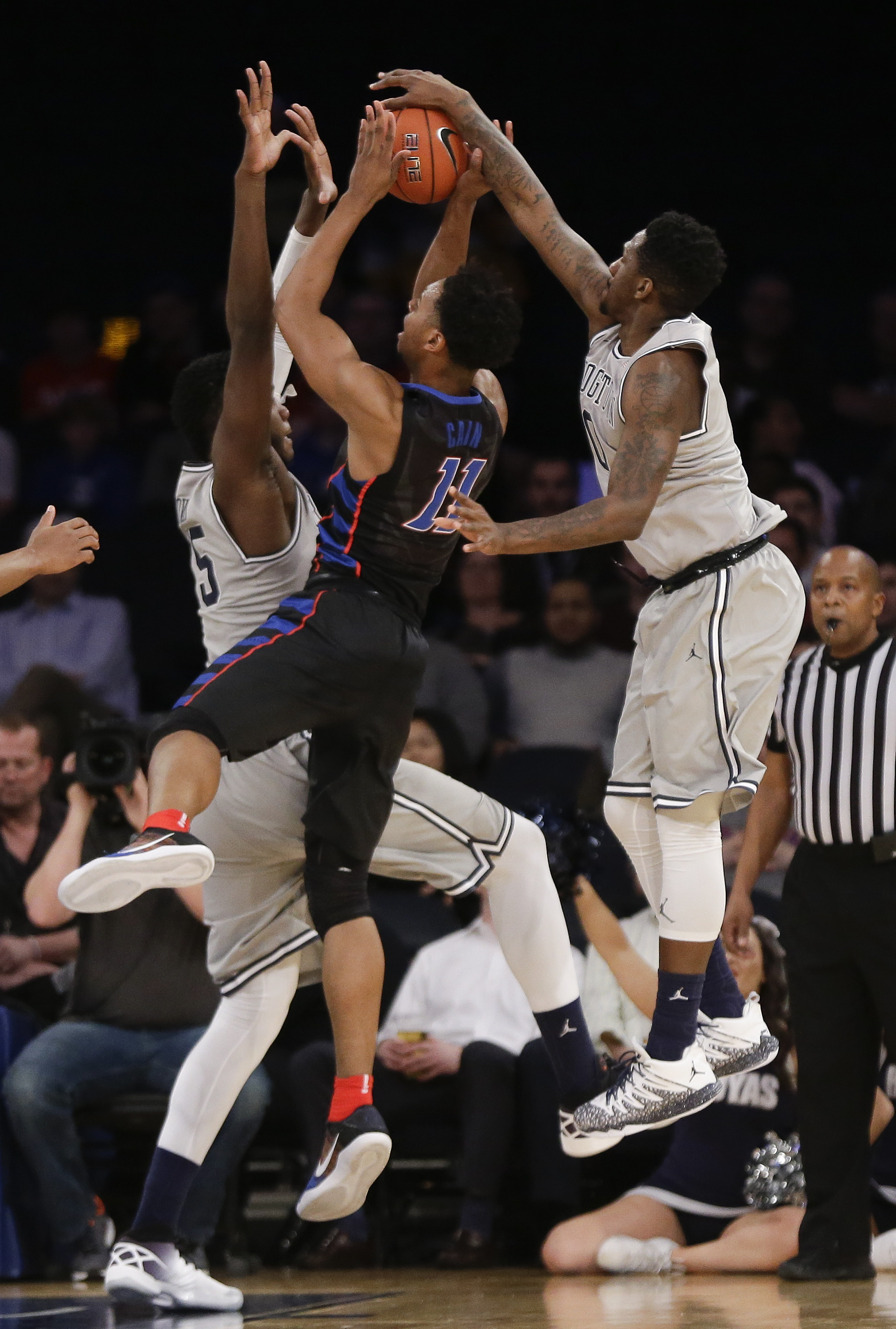 Georgetown guard L.J. Peak (0) blocks a shot by DePaul guard Eli Cain (11) as Georgetown center Jessie Govan (15) helps defend in the first half of an NCAA college basketball game during the Big East men's tournament, Wednesday, March 9, 2016, in New York