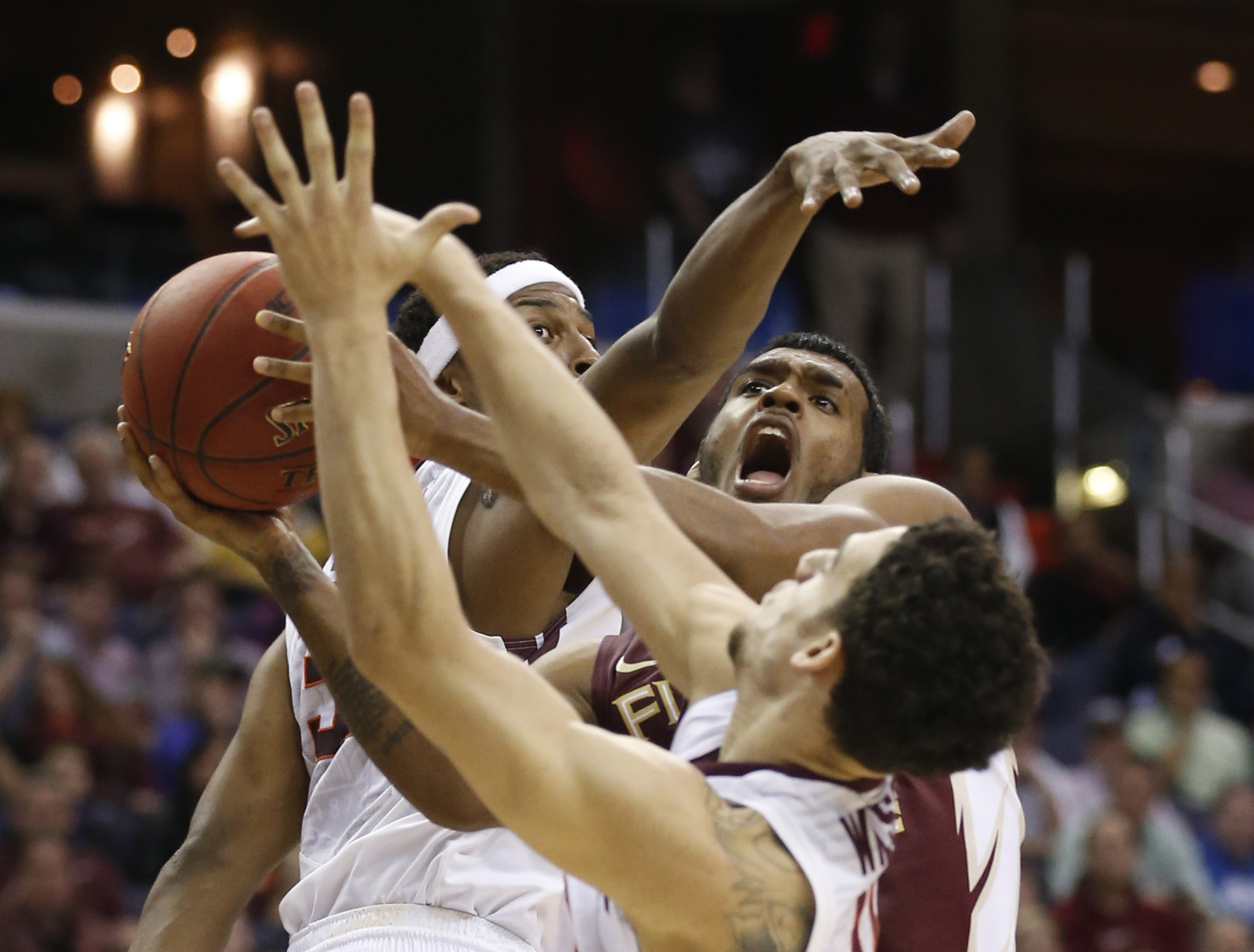 Florida State guard Xavier Rathan-Mayes, center, looks for a shot as Virginia Tech forward Zach LeDay, left, and guard Devin Wilson defend during the first half of an NCAA college basketball game in the Atlantic Coast Conference men's tournament Wednesday
