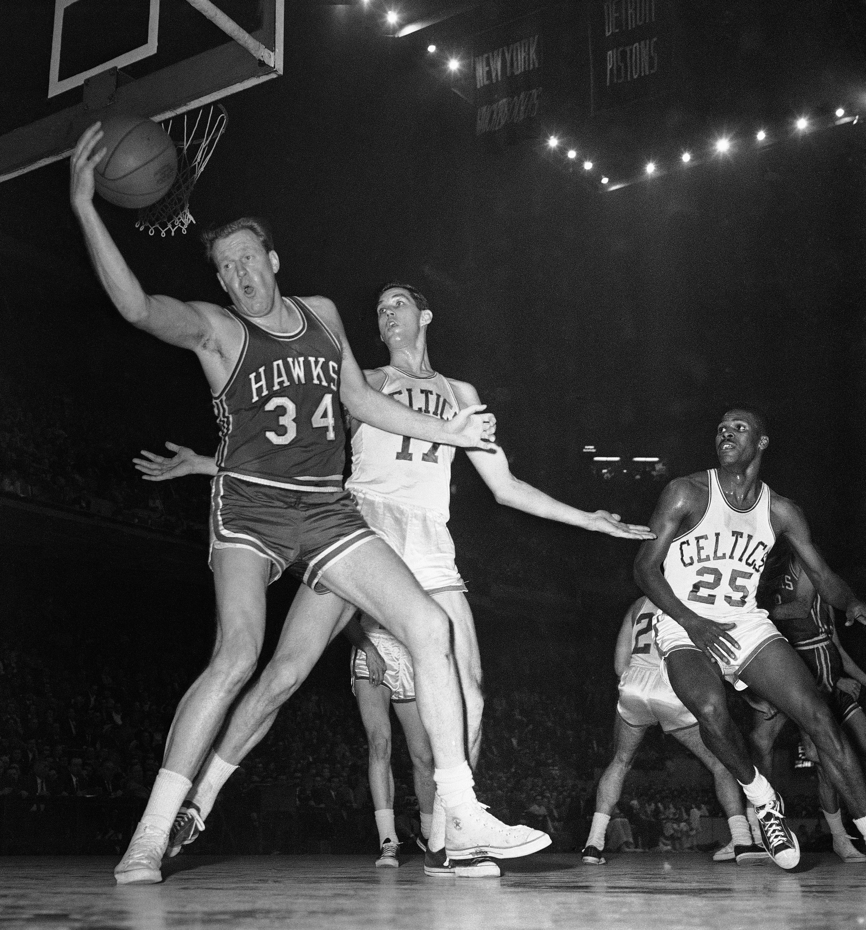 FILE - In this Jan. 13, 1960, file photo, St. Louis Hawks' Clyde Lovellette (34) snags ball from going out of bounds as Boston Celtics' Gene Conley defends during an NBA basketball game in Boston. Lovellette, the Hall of Fame forward who led Kansas to the