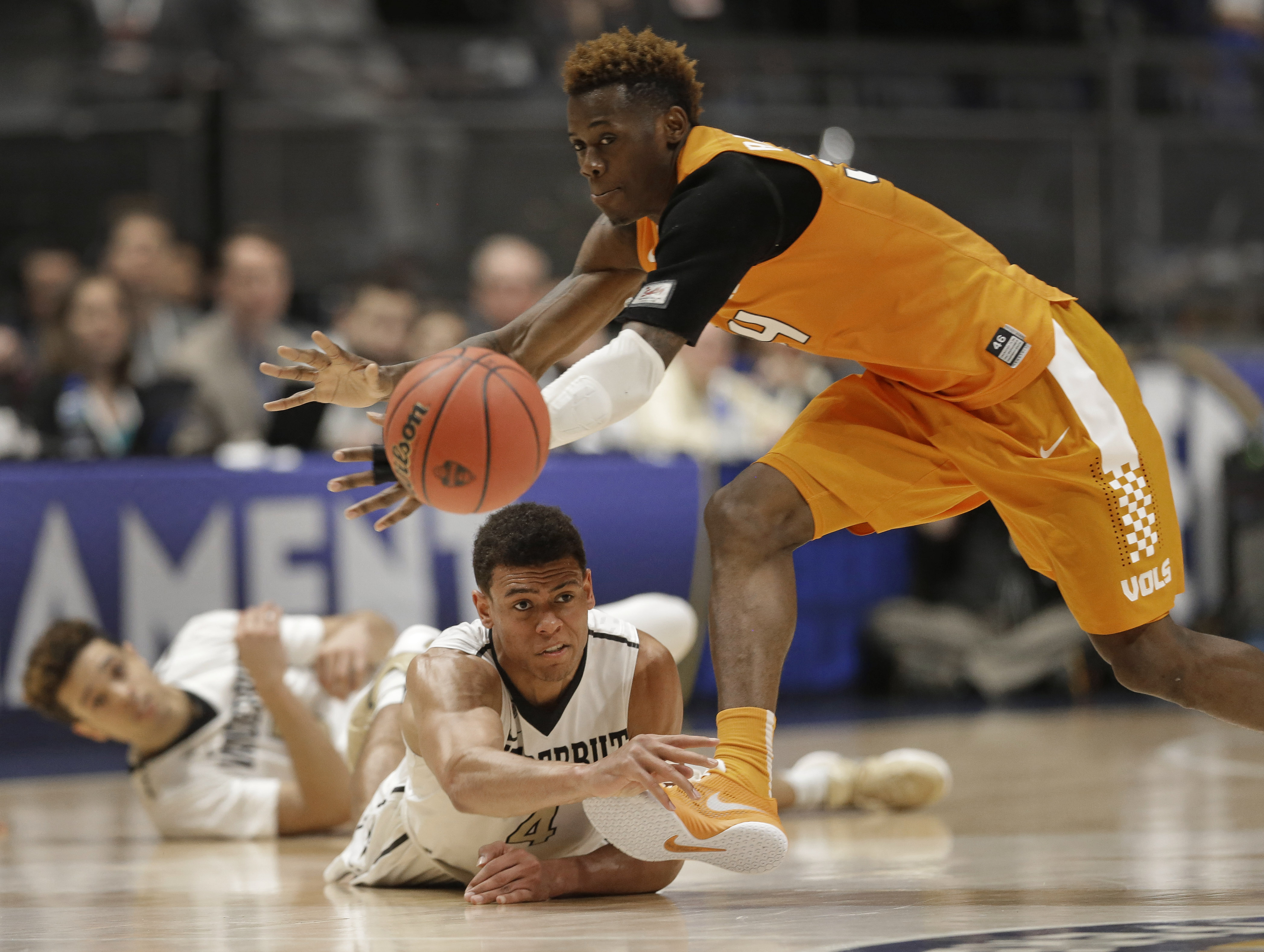 Vanderbilt's Wade Baldwin IV, bottom, passes a ball past Tennessee's Devon Baulkman (34) during the second half of an NCAA college basketball game in the Southeastern Conference tournament in Nashville, Tenn., Thursday, March 10, 2016. (AP Photo/Mark Hump