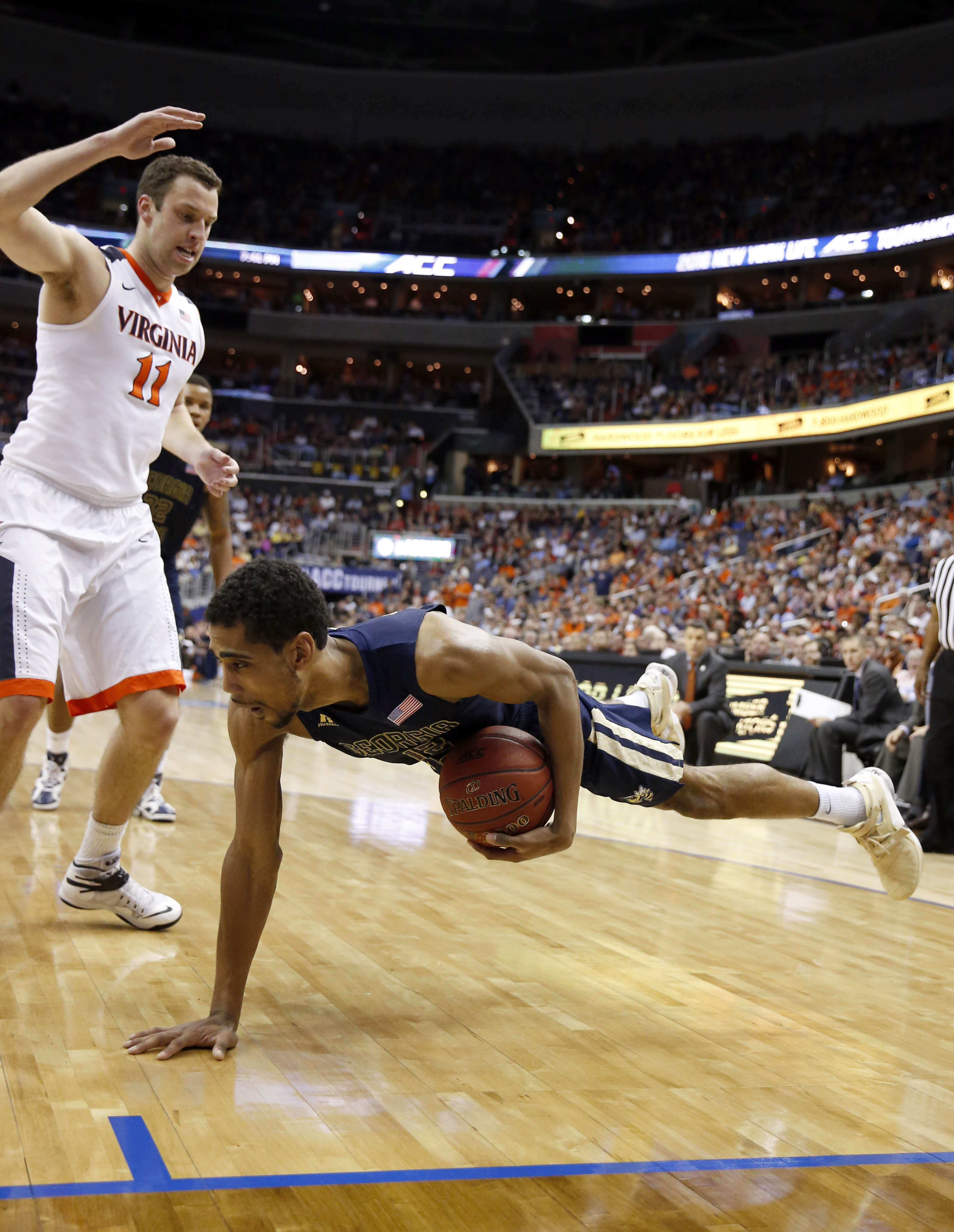 Georgia Tech forward Quinton Stephens (12) puts his hand out as he slips and falls in front of Virginia forward Evan Nolte (11) during the first half of an NCAA college basketball game in the Atlantic Coast Conference men's tournament, Thursday, March 10,