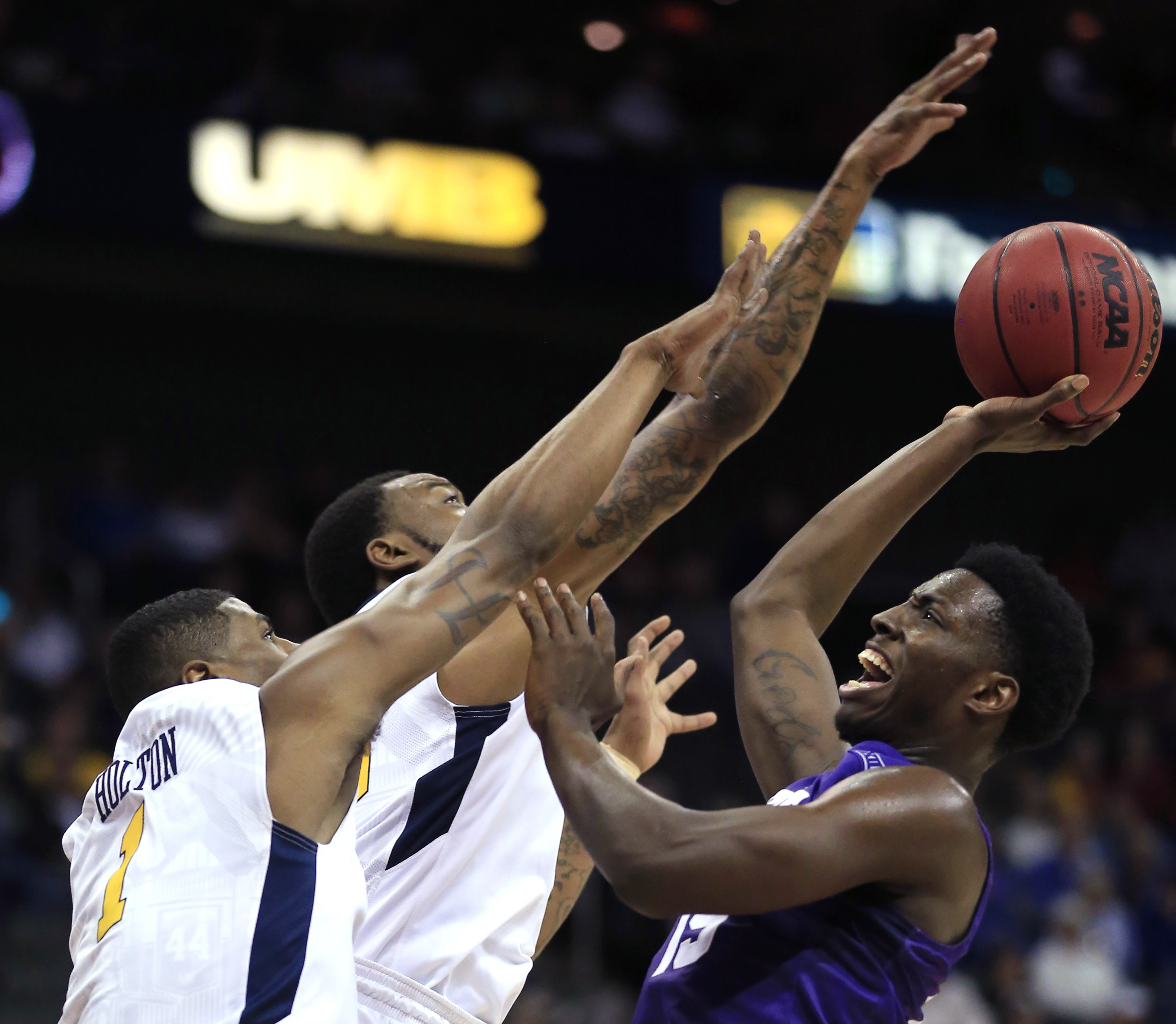 TCU forward JD Miller (15) shoots over West Virginia forwards Jonathan Holton (1) and Elijah Macon, middle, during the first half of an NCAA college basketball game in the quarterfinals of the Big 12 Conference men's tournament in Kansas City, Mo., Thursd