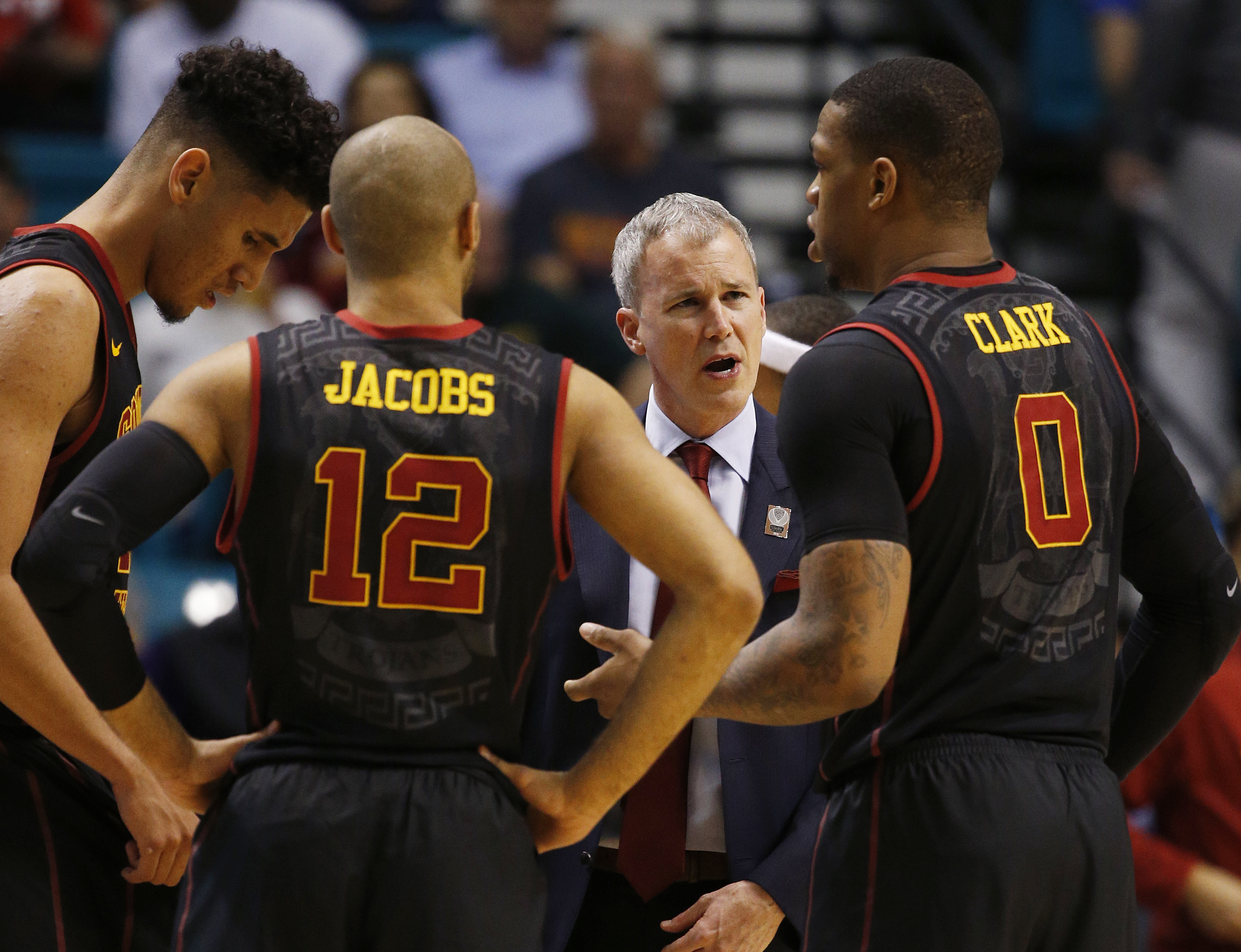 Southern California head coach Andy Enfield, second from right, speaks with forward Bennie Boatwright, left, guard Julian Jacobs, second from left, and Southern California forward Darion Clark during the second half of an NCAA college basketball game agai