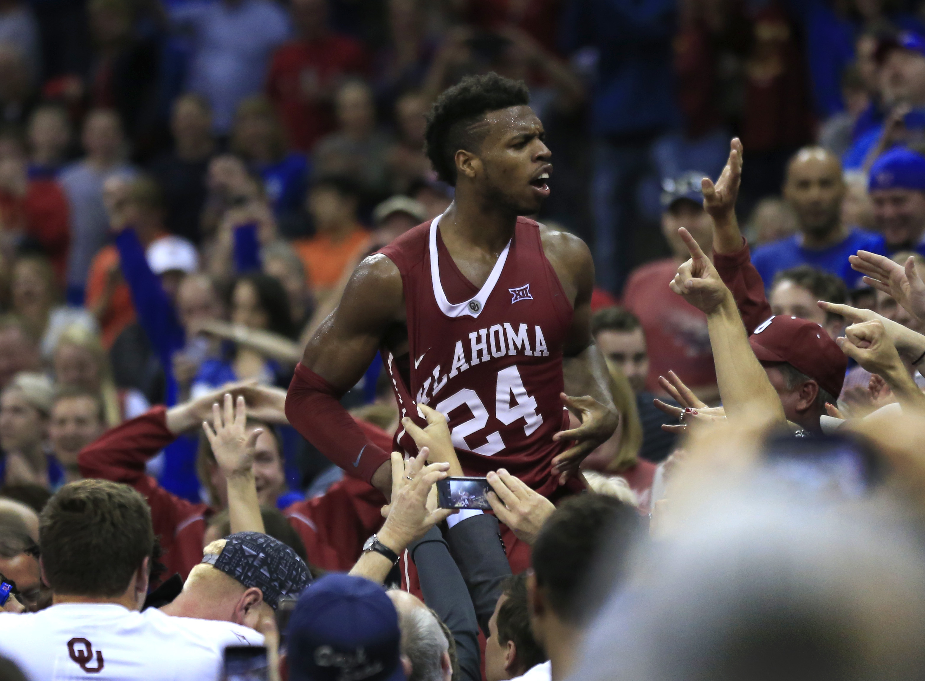 Oklahoma guard Buddy Hield (24) celebrates with fans after thinking he had scored the winning basket during NCAA college basketball game against West Virginia in the semifinals of the Big 12 conference men's tournament in Kansas City, Mo., Friday, March 1