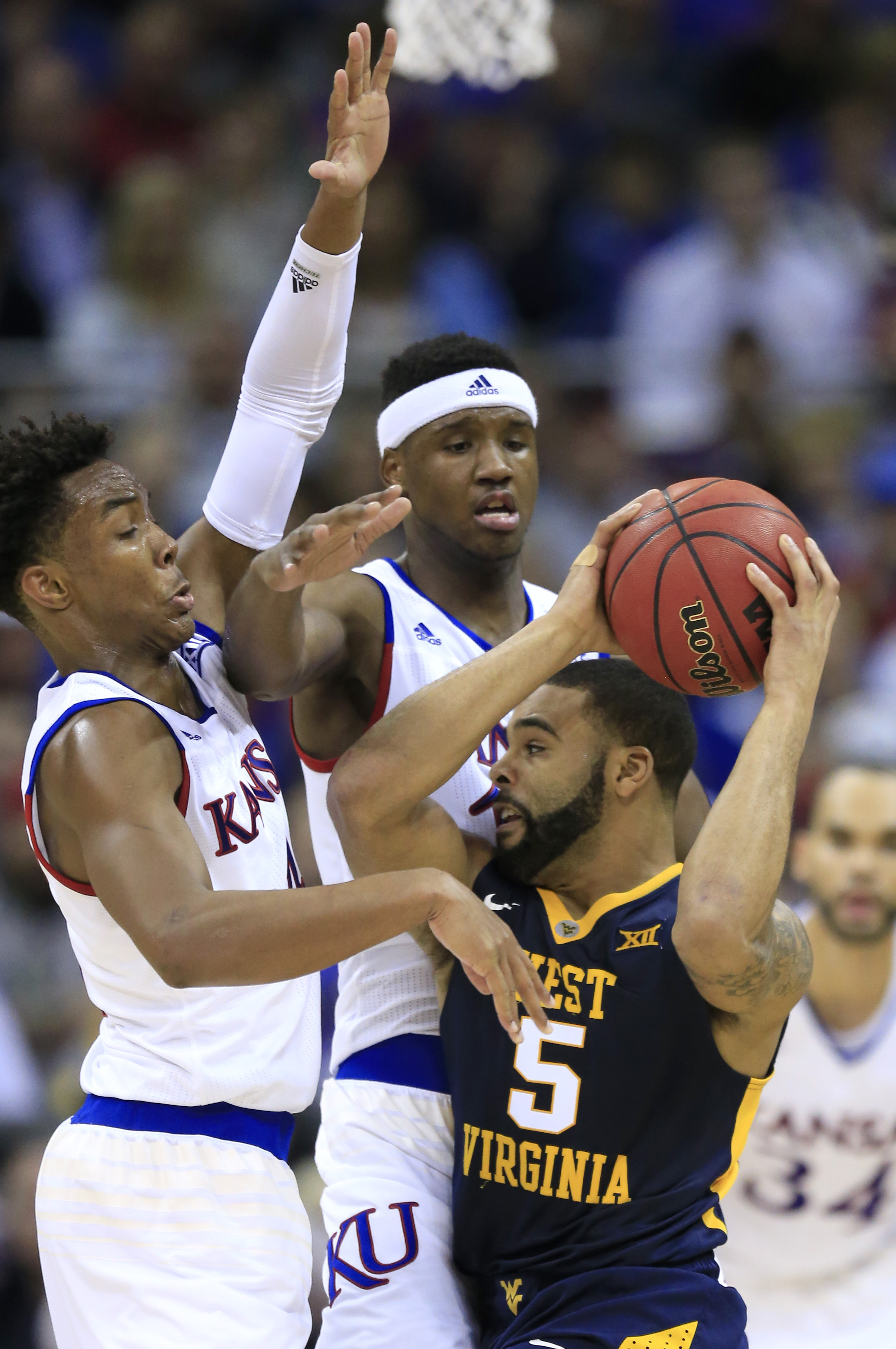 West Virginia guard Jaysean Paige (5) looks for help while covered by Kansas guard Devonte' Graham, left, and forward Carlton Bragg Jr., center, during the first half of an NCAA college basketball game in the finals of the Big 12 conference tournament in