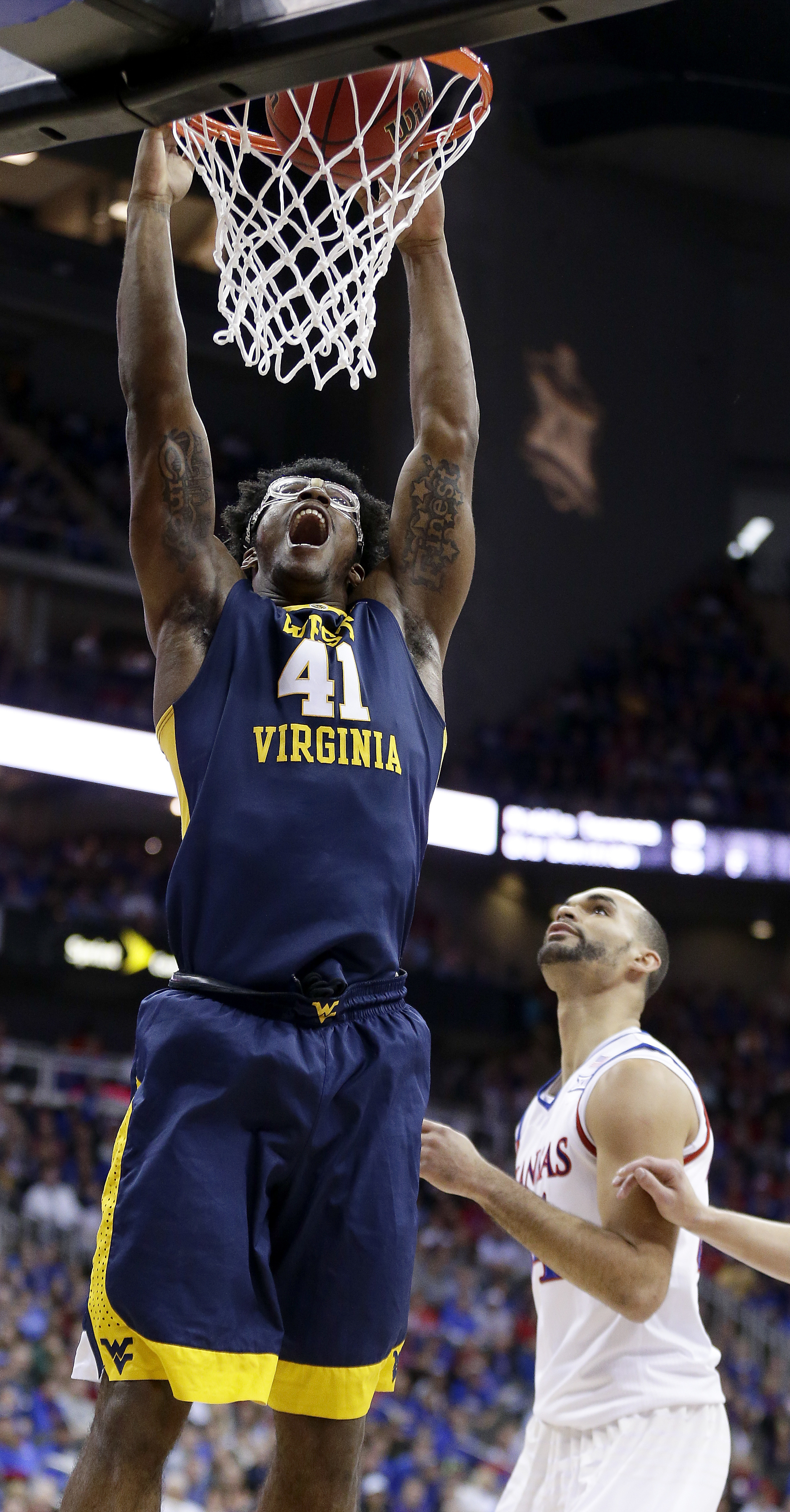 West Virginia's Devin Williams (41) gets past Kansas' Perry Ellis to dunk during the first half of an NCAA college basketball game in the final of the Big 12 conference men's tournament Saturday, March 12, 2016, in Kansas City, Mo. (AP Photo/Charlie Riede