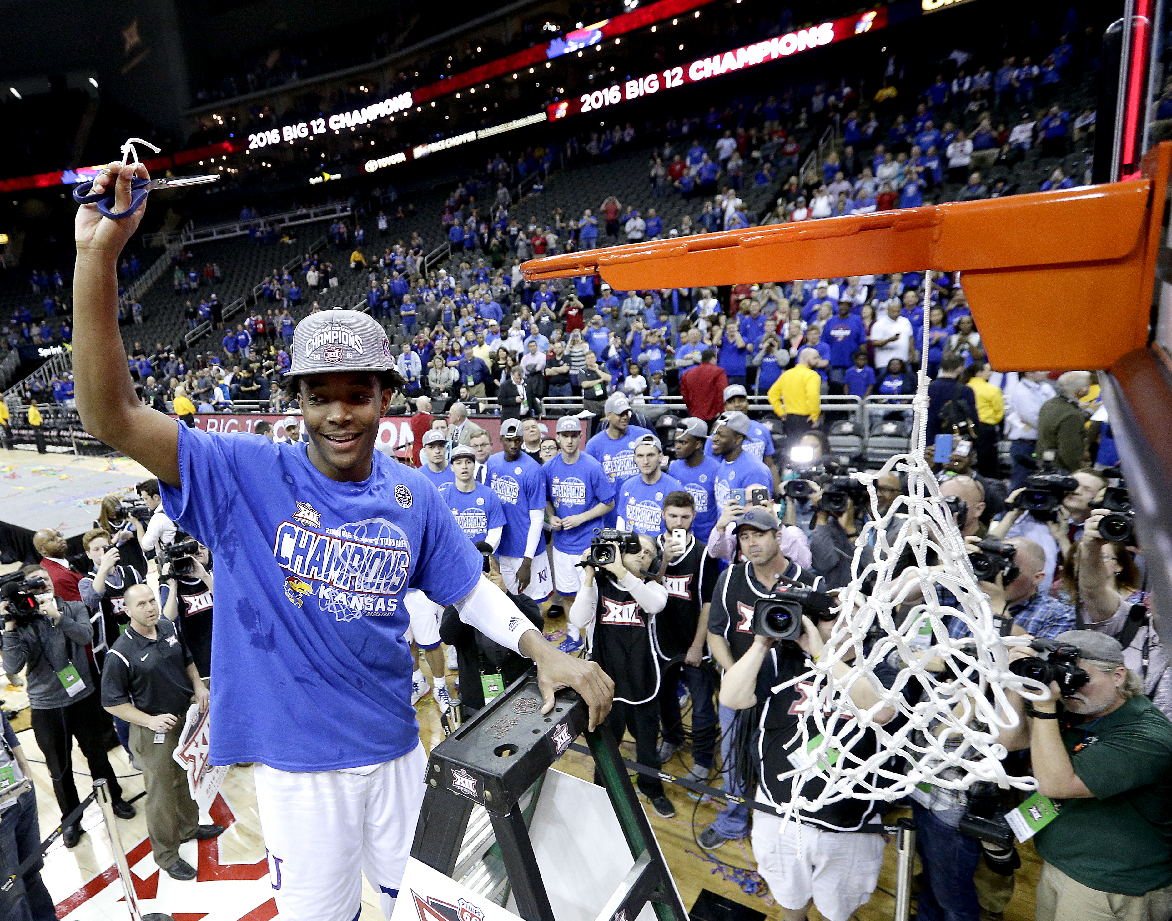 Kansas' Devonte' Graham cuts a piece of the net after winning an NCAA college basketball game against West Virginia to win the Big 12 conference tournament Saturday, March 12, 2016, in Kansas City, Mo. (AP Photo/Charlie Riedel)