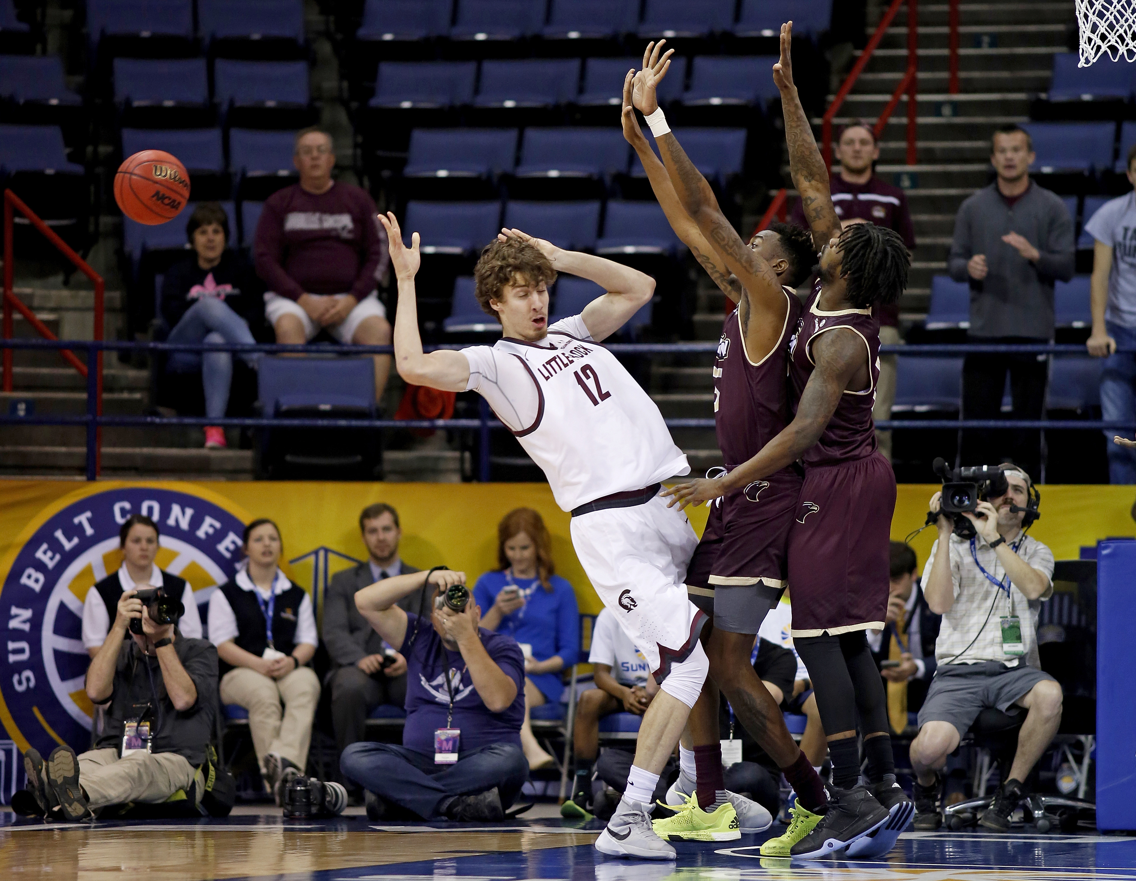 Arkansas Little Rock forward Lis Shoshi (12) loses control of the ball after a block from Louisiana Monroe forward DeMondre Harvey, right, and forward Jamaal Samuel, center, in the first half of an NCAA college basketball game in the championship of the S