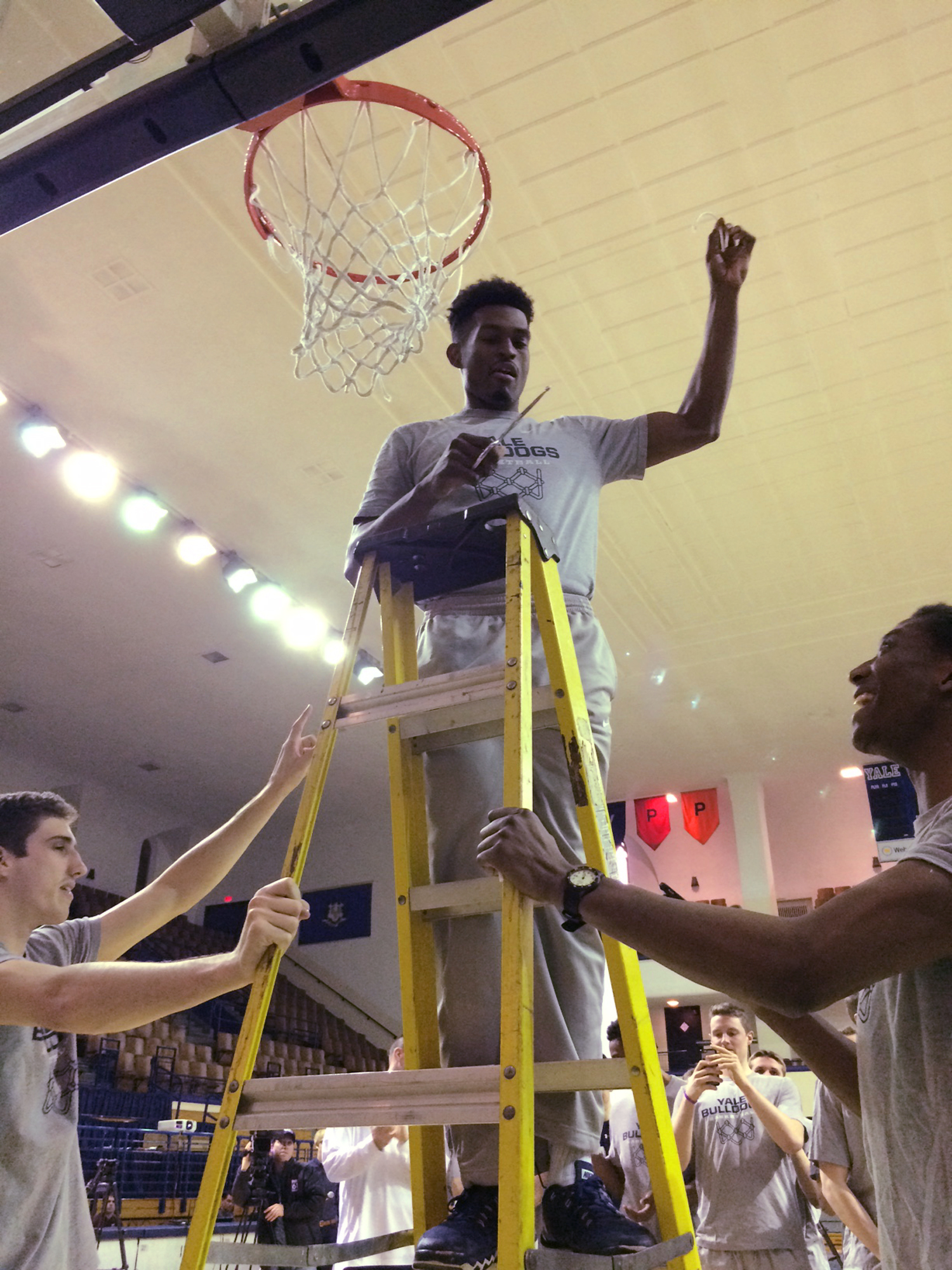 Brandon Sherrod helps cut down the net at Payne Whitney Gymnasium during Yale's tournament selection watch party in New Haven, Conn., Sunday, March 13, 2016. Yale has opened up the gym to the public and set up a movie screen at center court for fans to wa