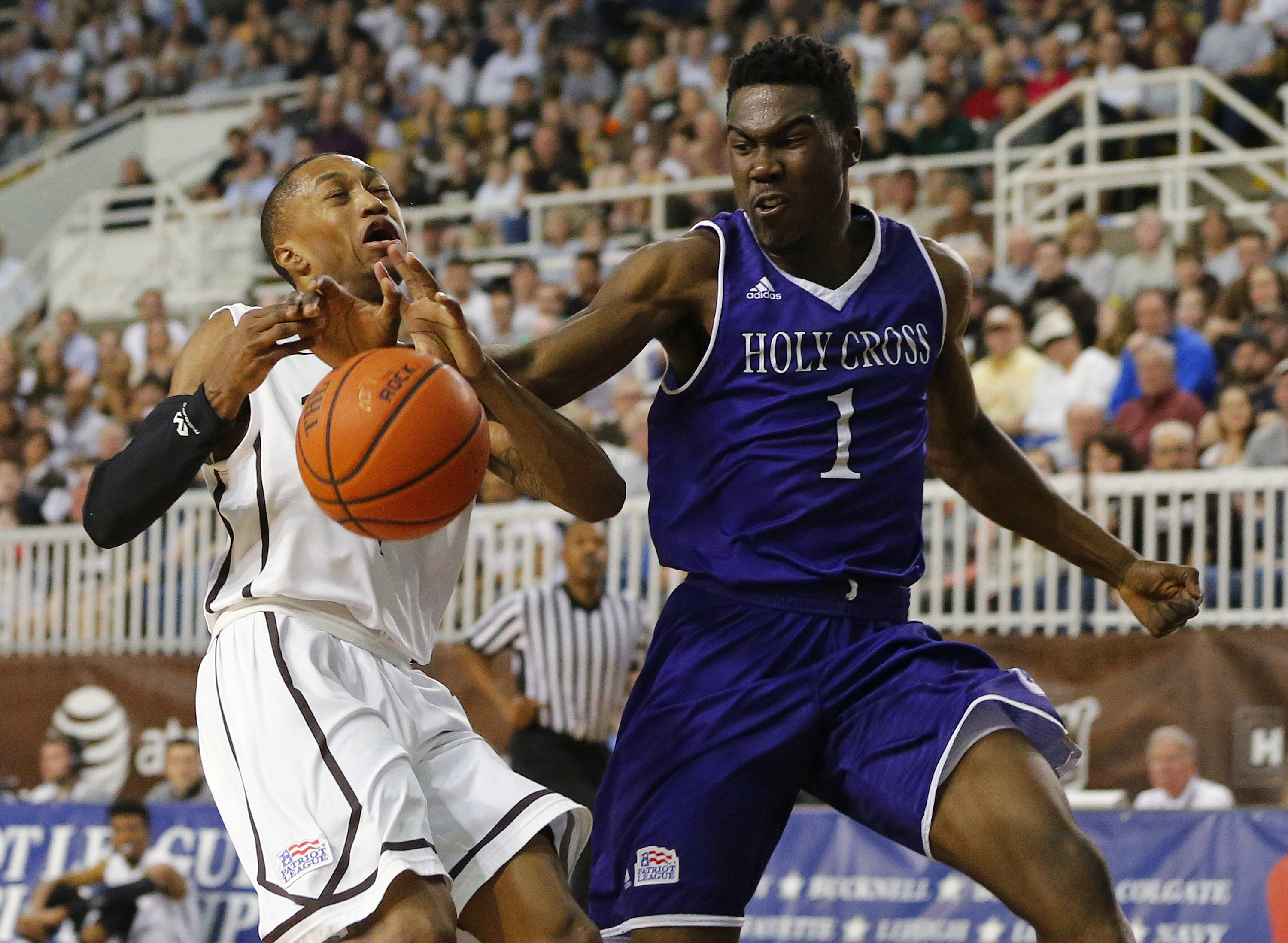 FILE- In this March 9, 2016, file photo, Lehigh guard Kahron Ross, left, has the ball knocked away from him by Holy Cross forward Karl Charles (1) during the first half of the NCAA college basketball Patriot League Championship game at Lehigh in Bethlehem