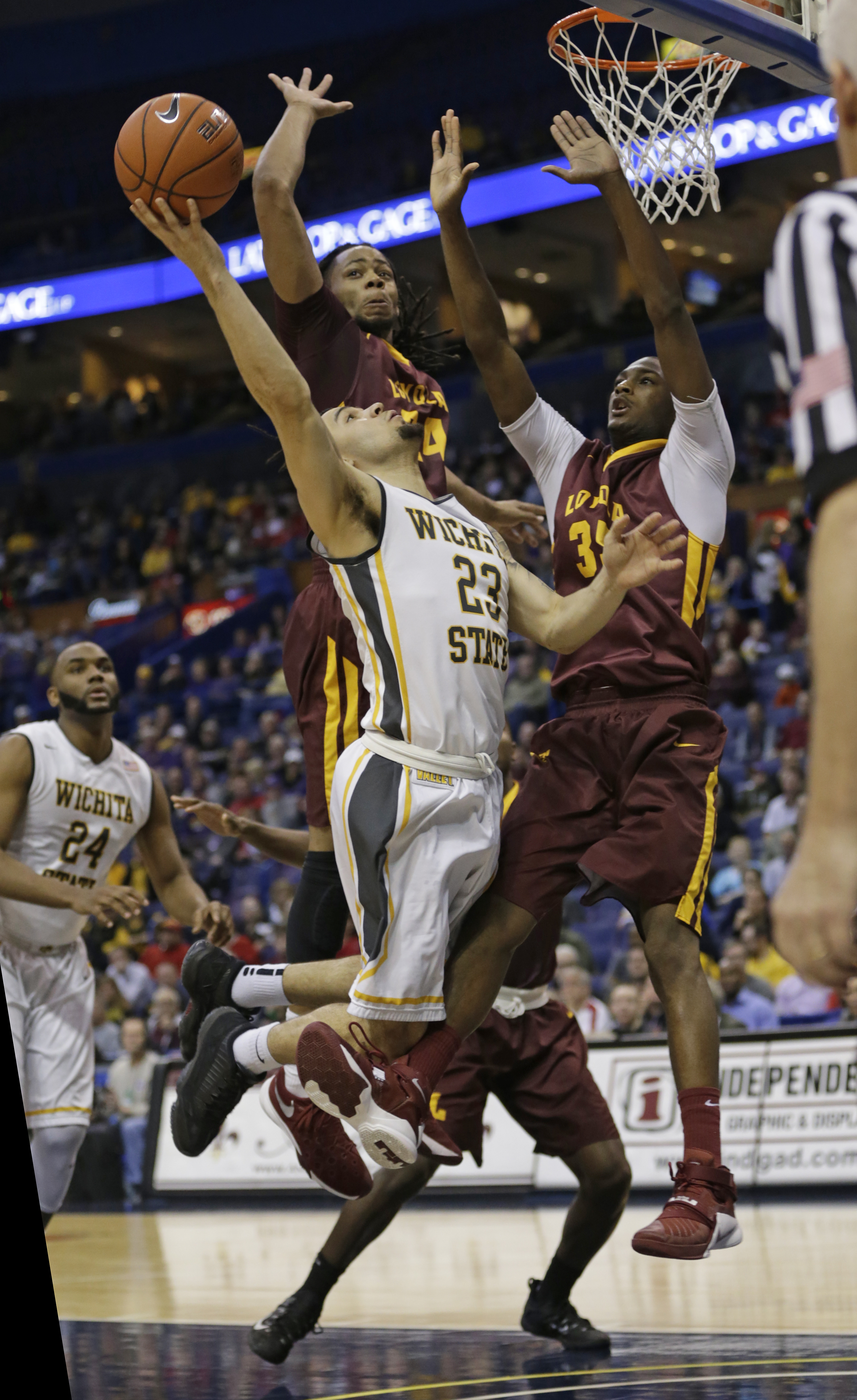 FILE - In this March 4, 2016, file photo, Wichita State's Fred VanVleet (23) goes to the basket as Loyola Chicago's Montel James (24) and Milton Doyle (35), right, defend during the second half of an NCAA college basketball game in the quarterfinals of th