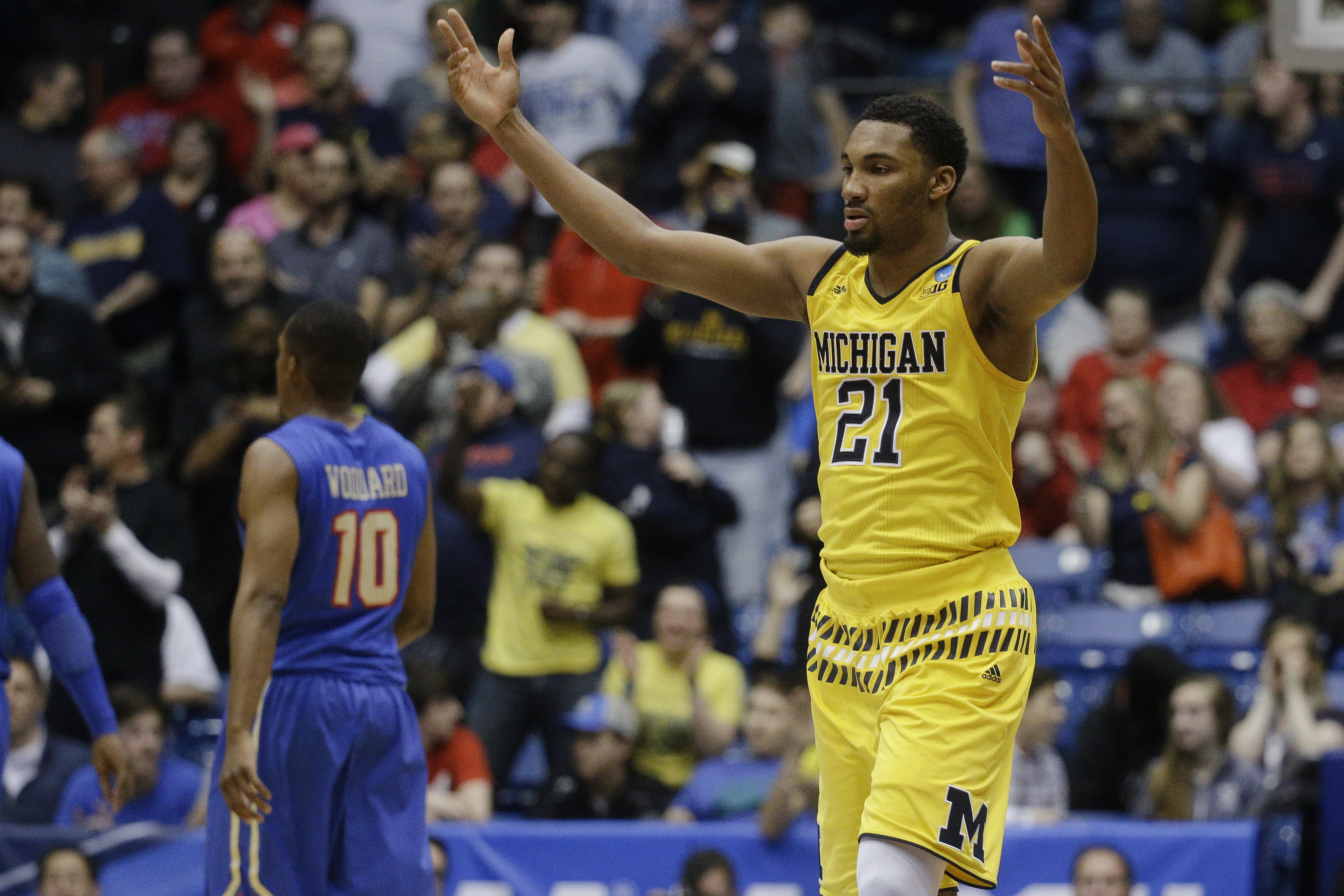 Michigan's Zak Irvin (21) celebrates during the second half of a First Four game of the NCAA college basketball tournament against Tulsa, Wednesday, March 16, 2016, in Dayton, Ohio. Michigan won 67-62. (AP Photo/John Minchillo)