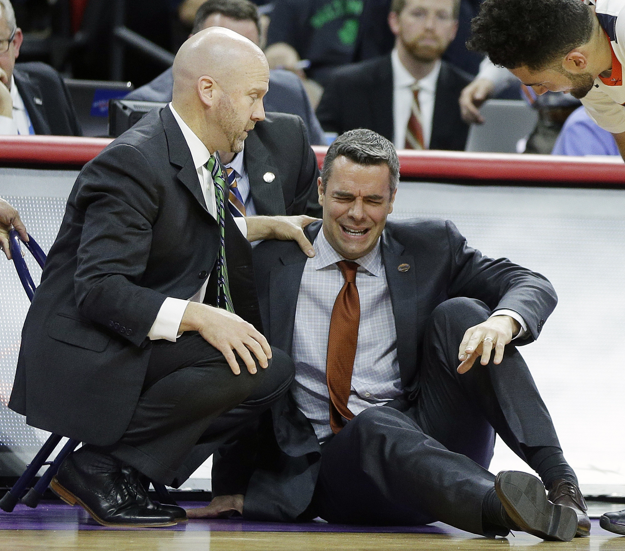 Virginia head coach Tony Bennett is attended to after Bennett collapsed during play against Hampton during the first half of a first-round men's college basketball game in the NCAA Tournament, Thursday, March 17, 2016, in Raleigh, N.C. (AP Photo/Chuck Bur