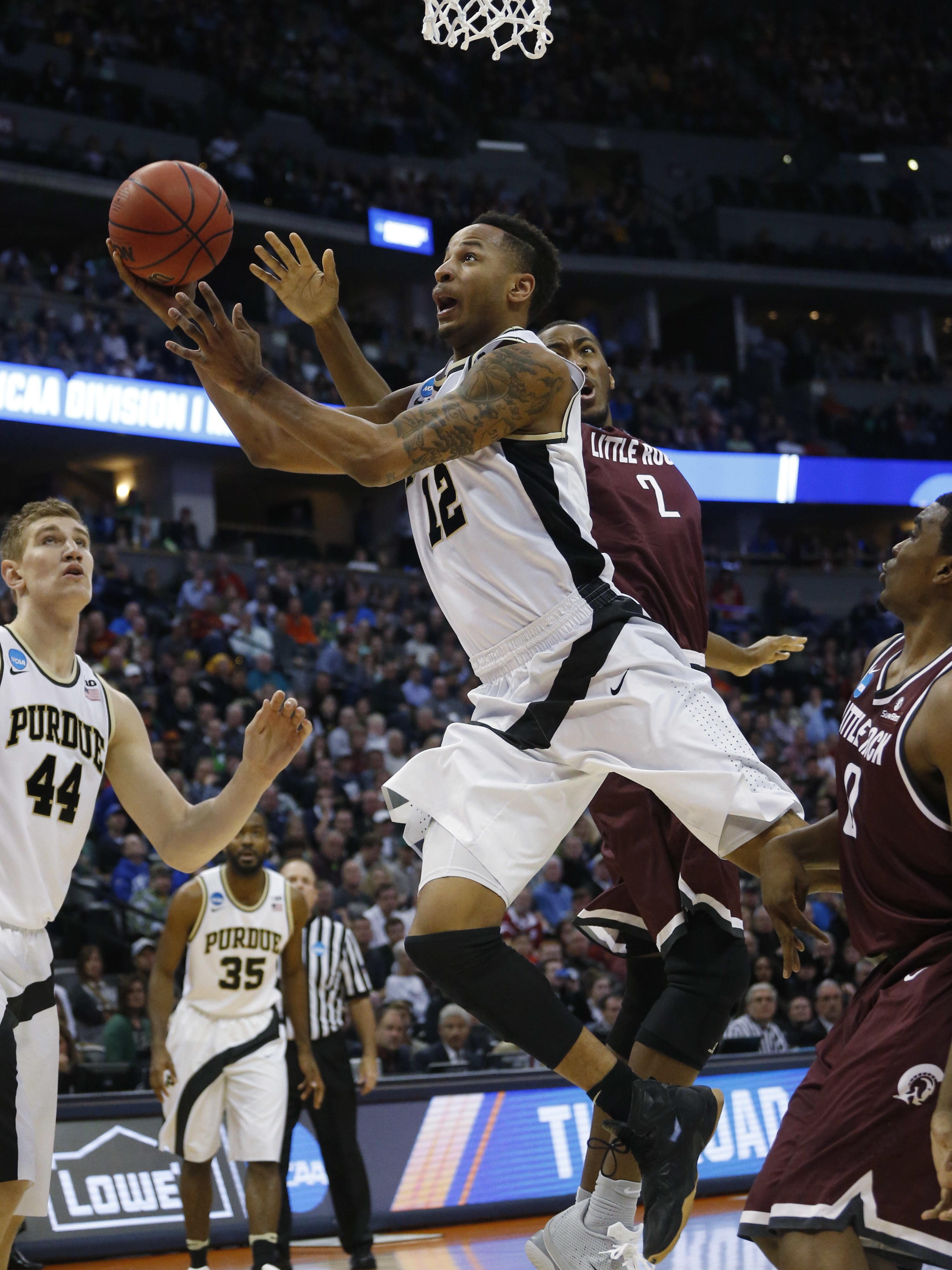Purdue forward Vince Edwards, front, drives for a basket as Arkansas Little Rock forward Daniel Green defends in the first half of a first-round men's college basketball game Thursday, March 17, 2016, in the NCAA Tournament in Denver. (AP Photo/Brennan Li