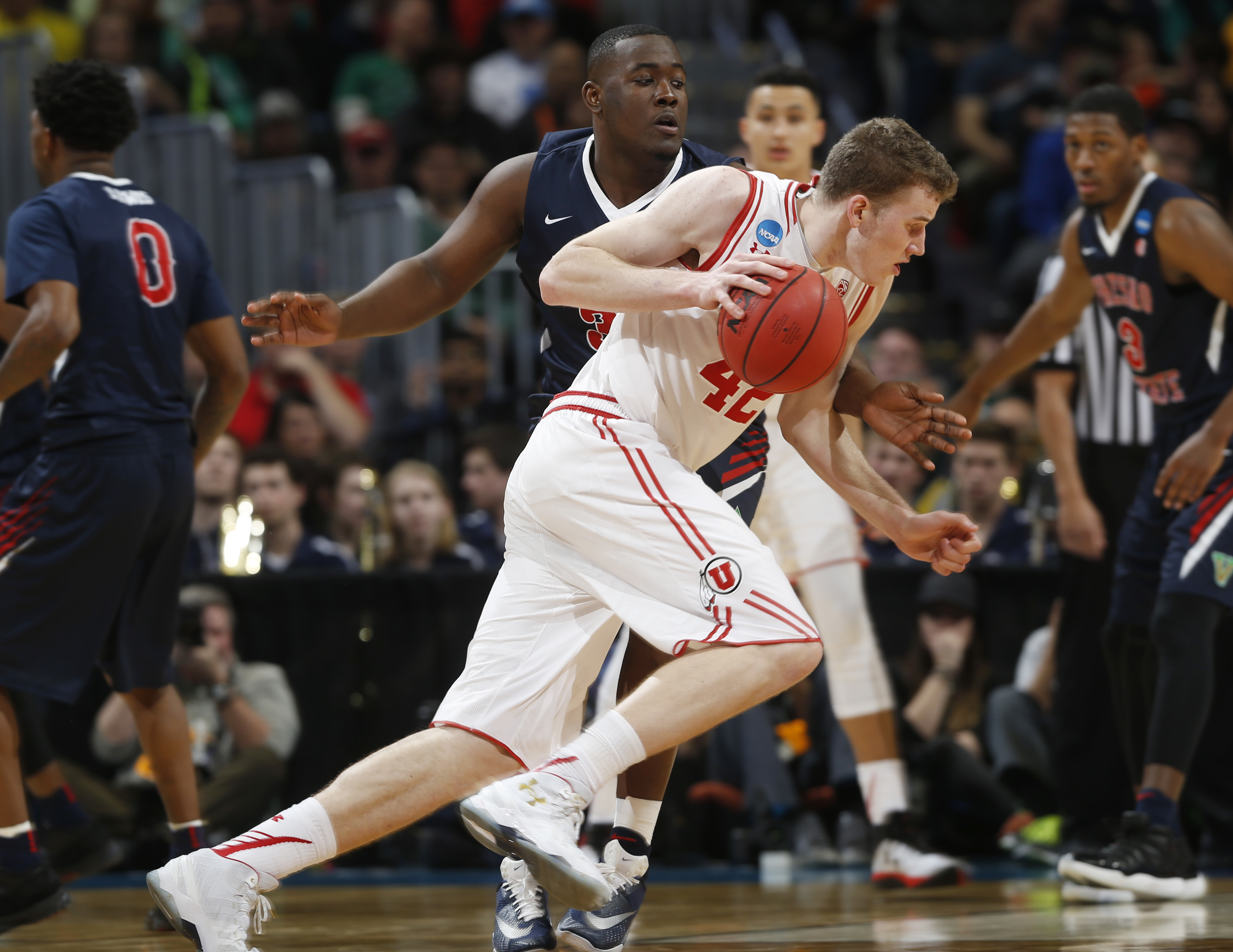 Utah forward Jakob Poeltl, front, drives past Fresno State center Terrell Carter II in the second half of a first-round men's college basketball game Thursday, March 17, 2016, in the NCAA Tournament in Denver. Utah won 80-69. (AP Photo/David Zalubowski)