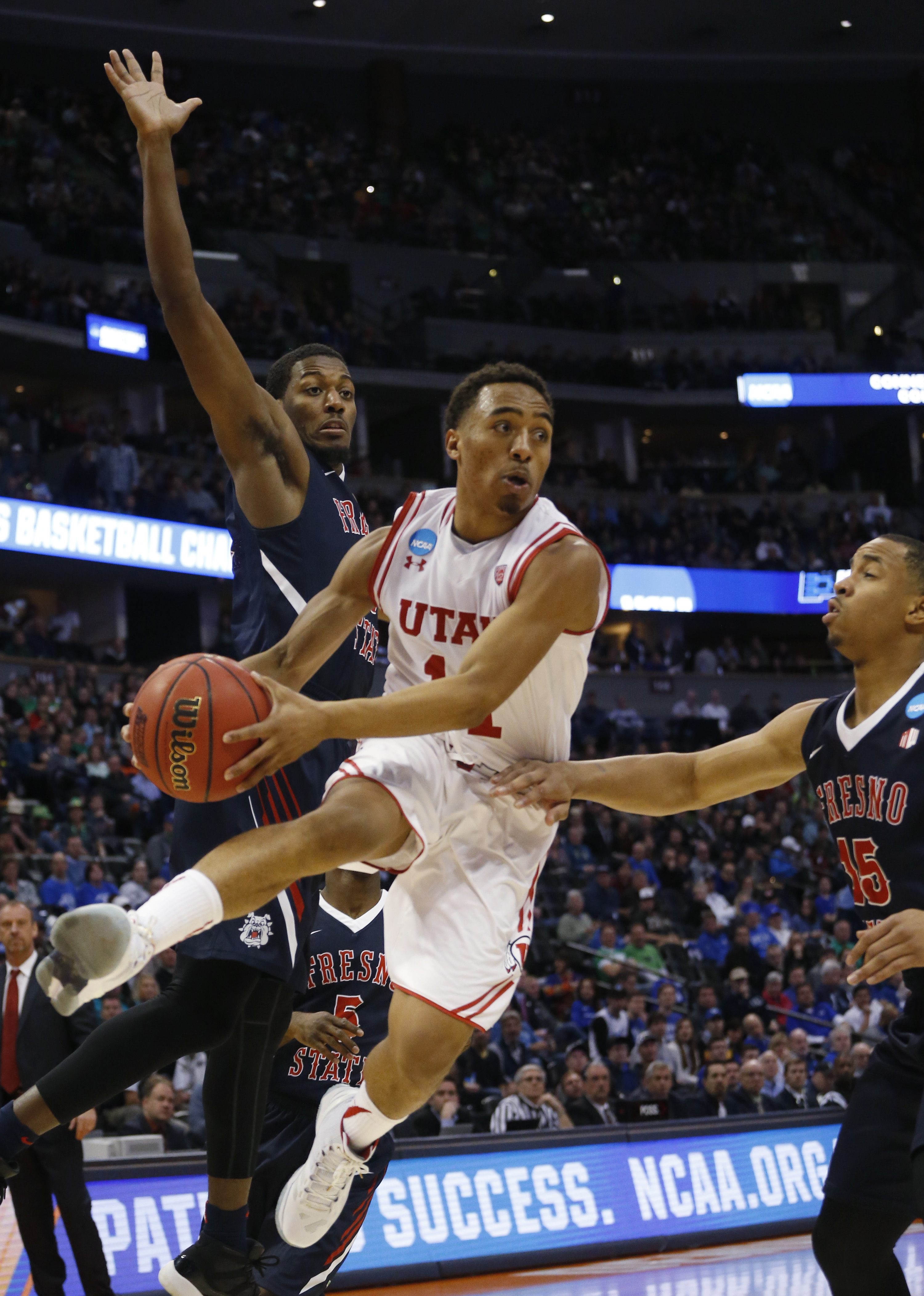 Utah guard Brandon Taylor, center, drives past Fresno State guards Paul Watson, left, and Lionel Ellison III for a shot in the second half of a first-round men's college basketball game Thursday, March 17, 2016, in the NCAA Tournament in Denver. Utah won