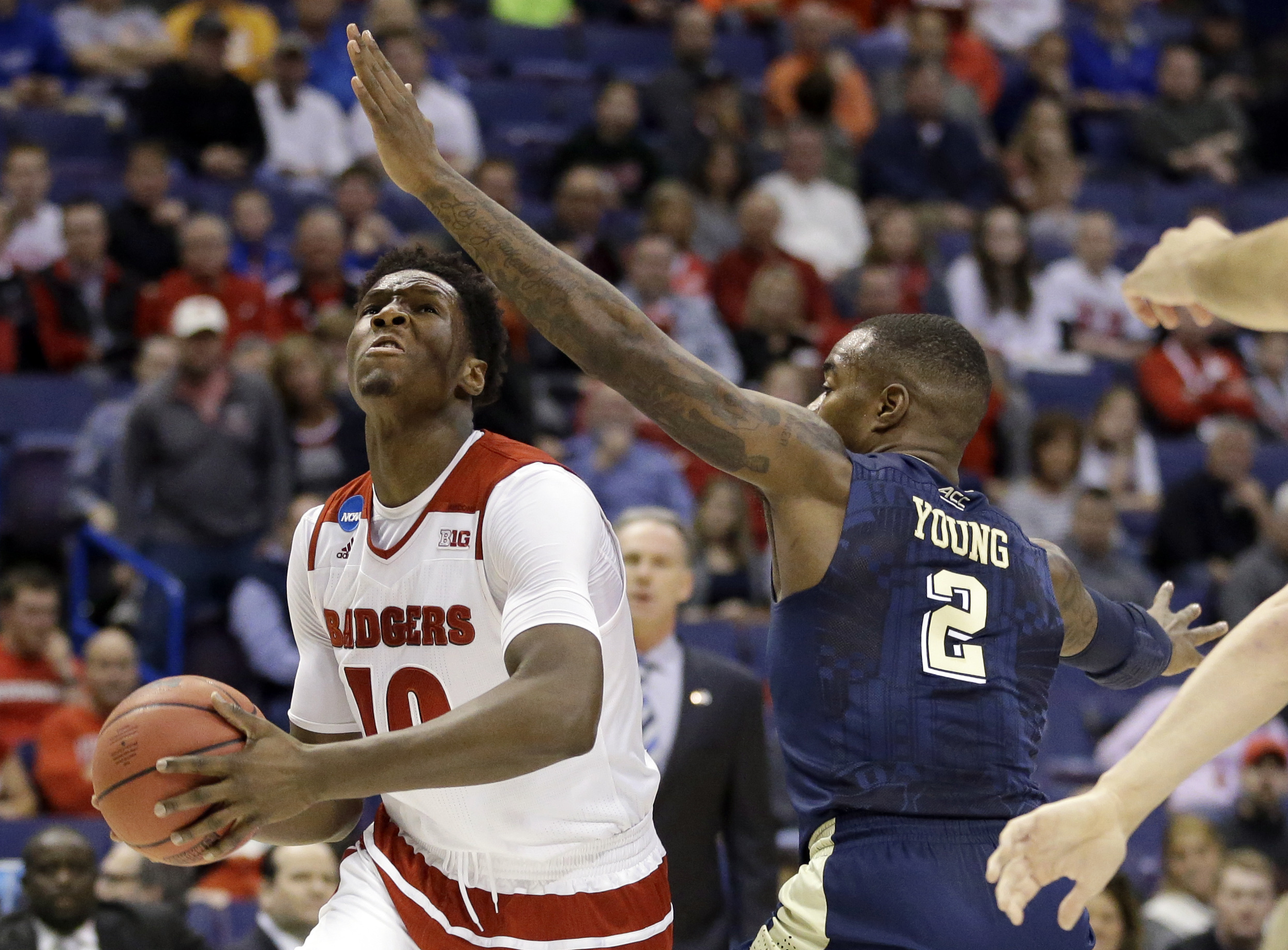 Wisconsin's Nigel Hayes, left, heads to the basket as Pittsburgh's Michael Young defends during the first half in a first-round men's college basketball game in the NCAA tournament, Friday, March 18, 2016, in St. Louis. (AP Photo/Jeff Roberson)