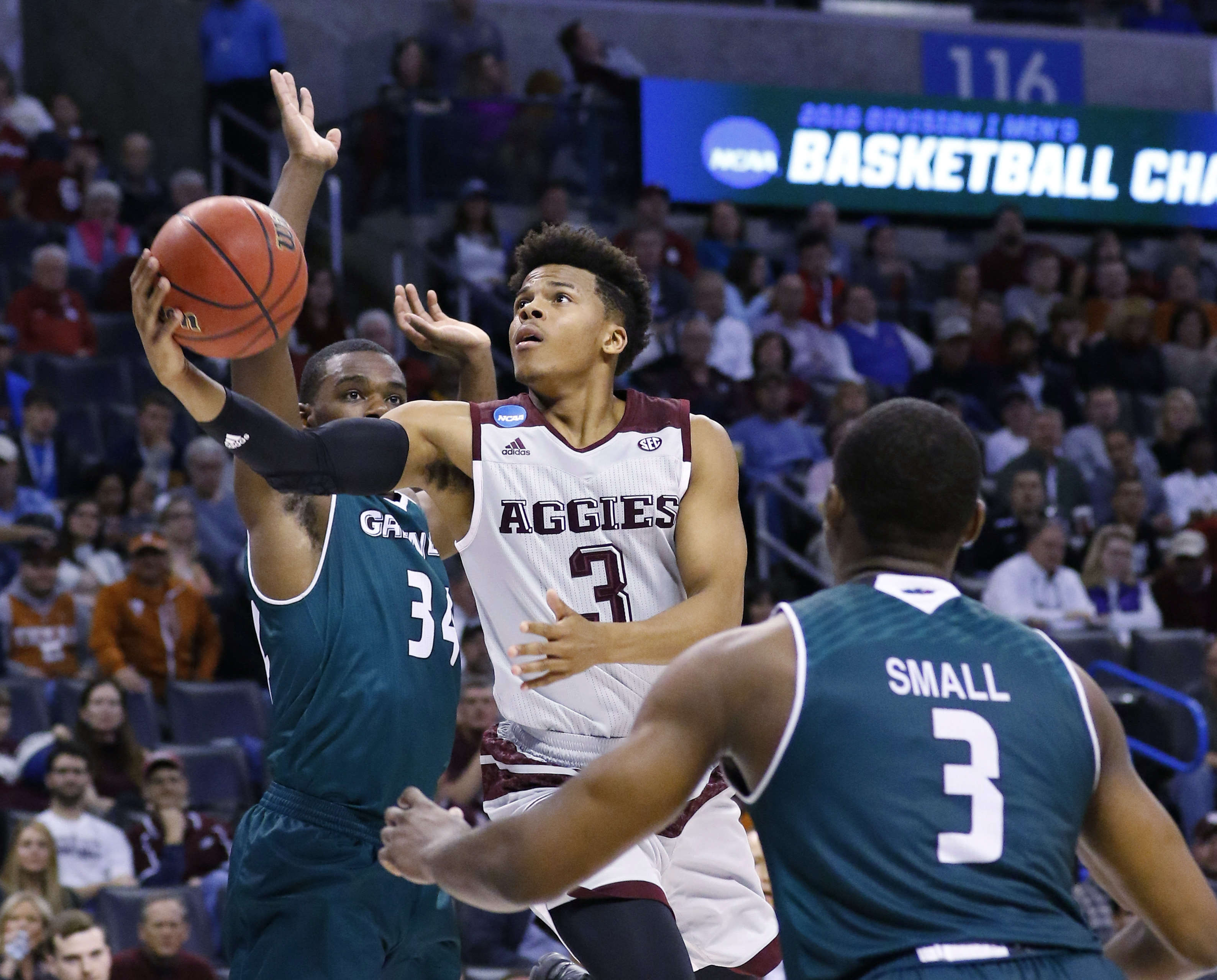 Texas A&M guard Admon Gilder (3) shoots between Green Bay guard Charles Cooper (34) and guard Khalil Small (3) in the second half of a first-round men's college basketball game in the NCAA Tournament, Friday, March 18, 2016, in Oklahoma City. Texas A&M wo