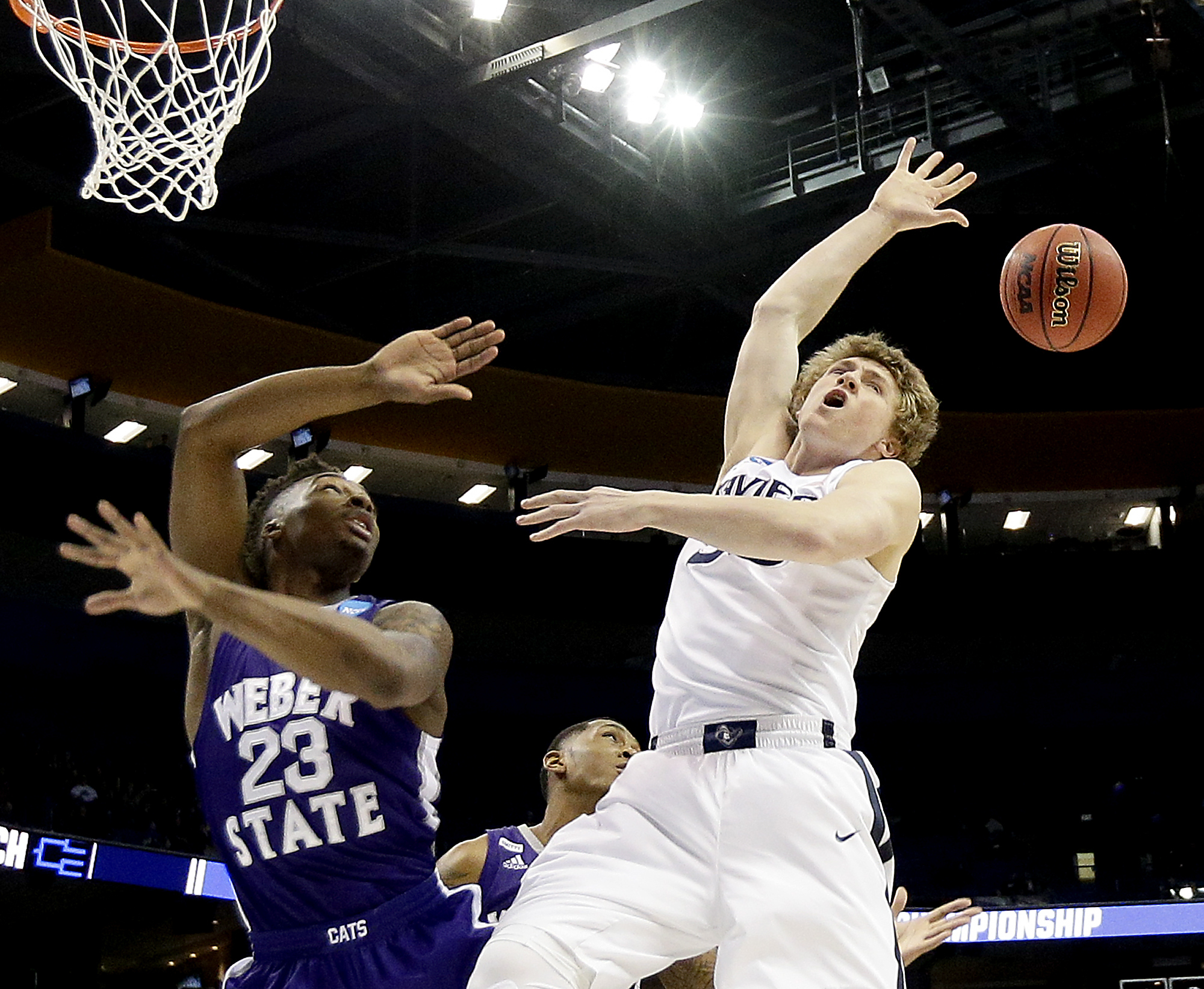 Weber State's Richaud Gittens (23) knocks the ball away from Xavier's Trevon Bluiett during the first half of a first-round men's college basketball game in the NCAA Tournament, Friday, March 18, 2016, in St. Louis. (AP Photo/Charlie Riedel)
