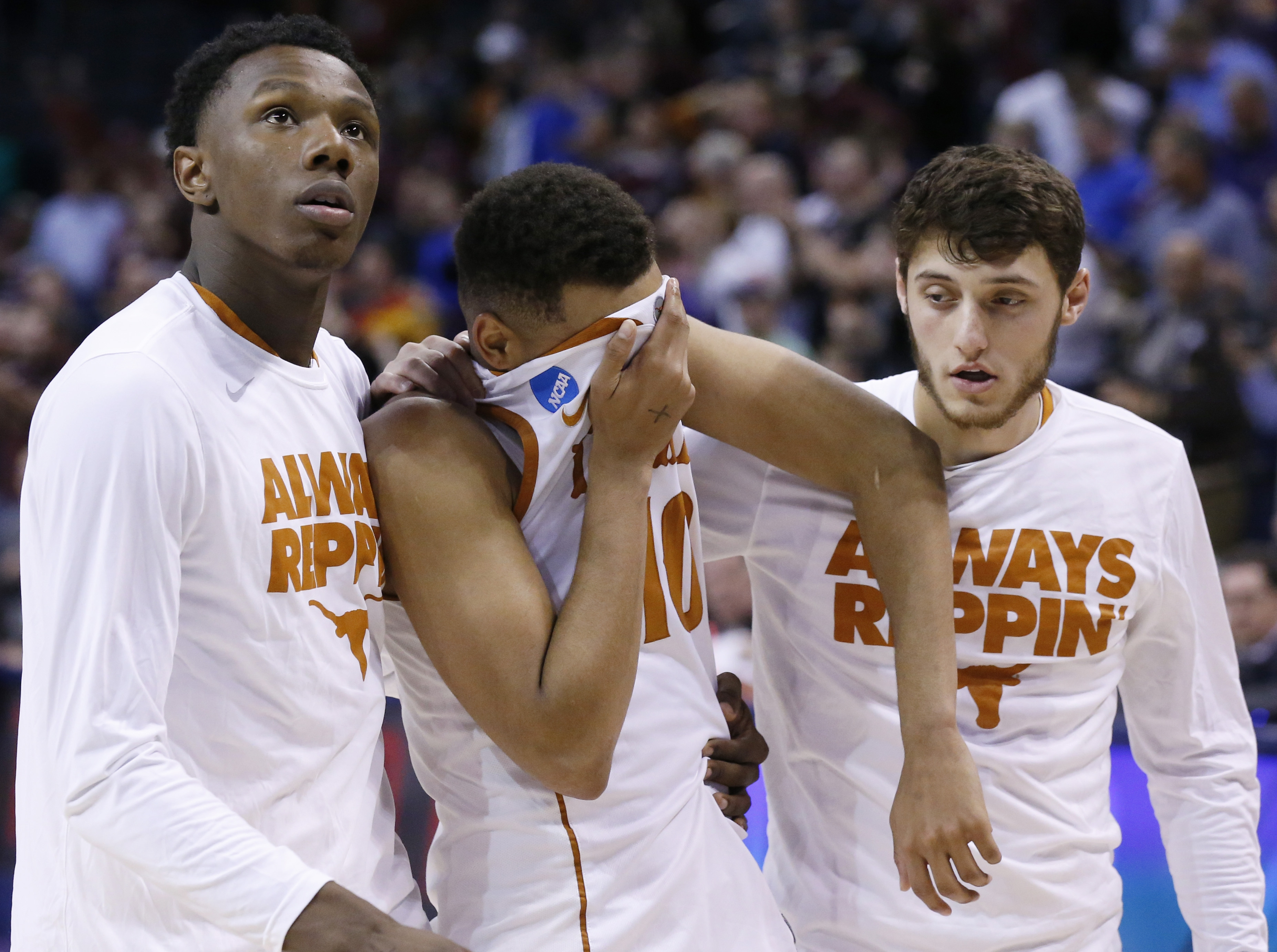 Texas guard Eric Davis Jr., center, is helped off the court by teammates Tevin Mack, left, and Joe Schwartz, right, after a first-round men's college basketball game against Northern Iowa in the NCAA Tournament, Friday, March 18, 2016, in Oklahoma City. N