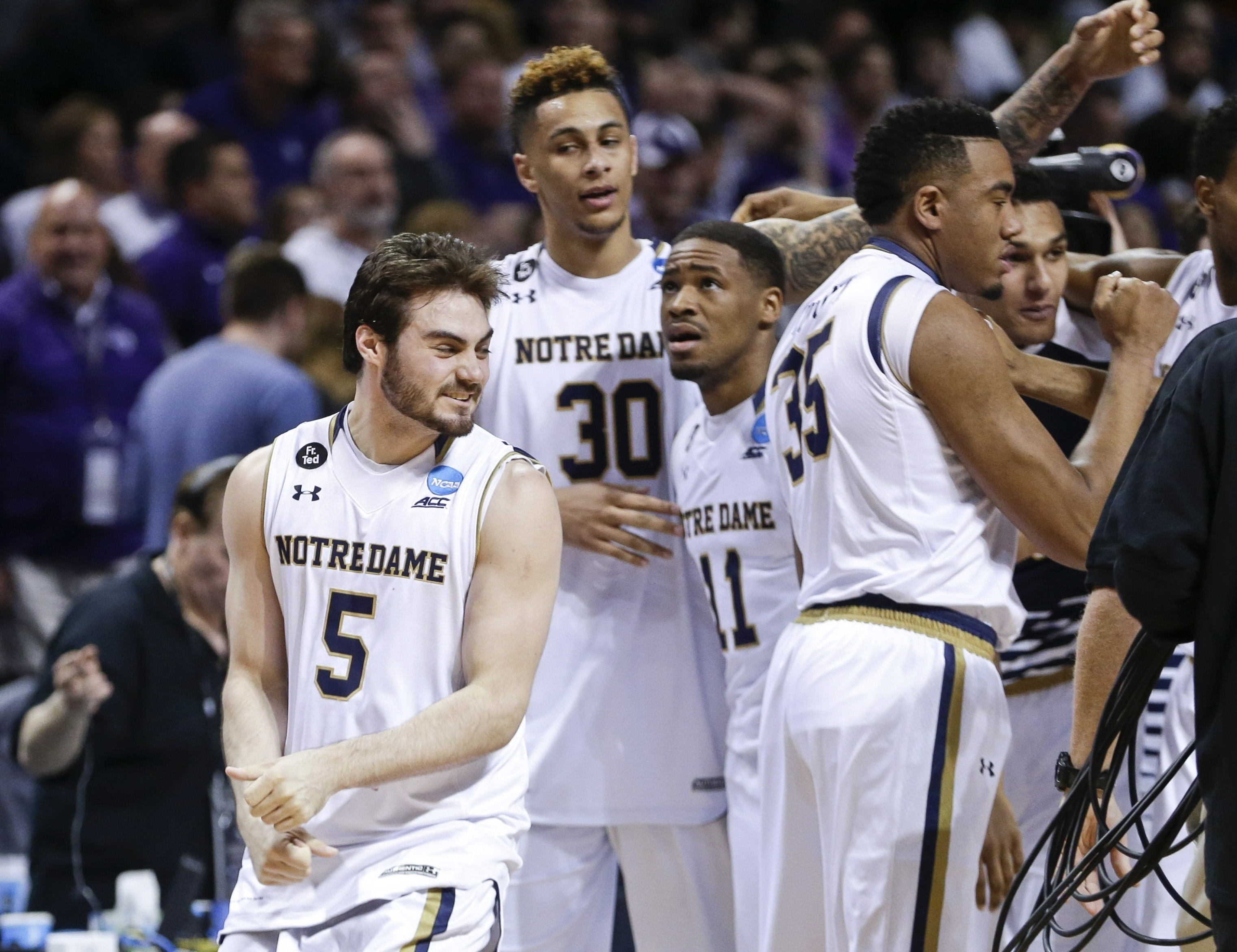 Notre Dame's Matt Farrell (5), Zach Auguste (30) and Demetrius Jackson (11) celebrate with teammates after a second-round men's college basketball game against Stephen F. Austin in the NCAA Tournament, Sunday, March 20, 2016, in New York.  (AP Photo/Frank
