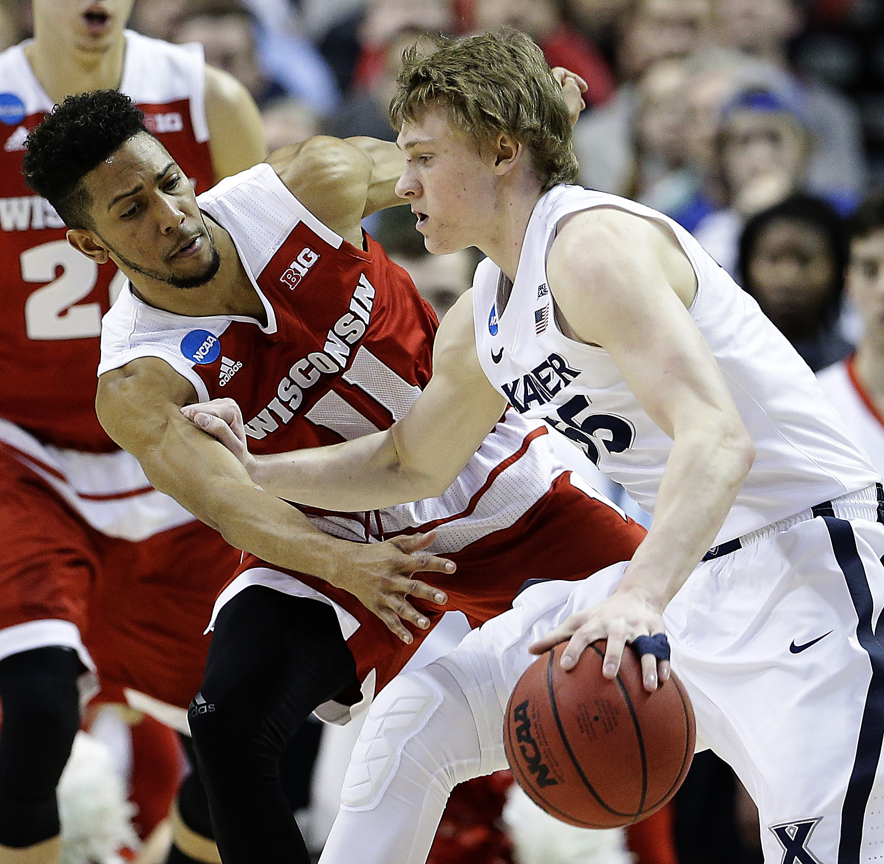 Wisconsin's Jordan Hill (11) tries to steal the ball from Xavier's J.P. Macura (55) during the first half of a second-round men's college basketball game against Wisconsin in the NCAA Tournament, Sunday, March 20, 2016, in St. Louis. (AP Photo/Charlie Rie
