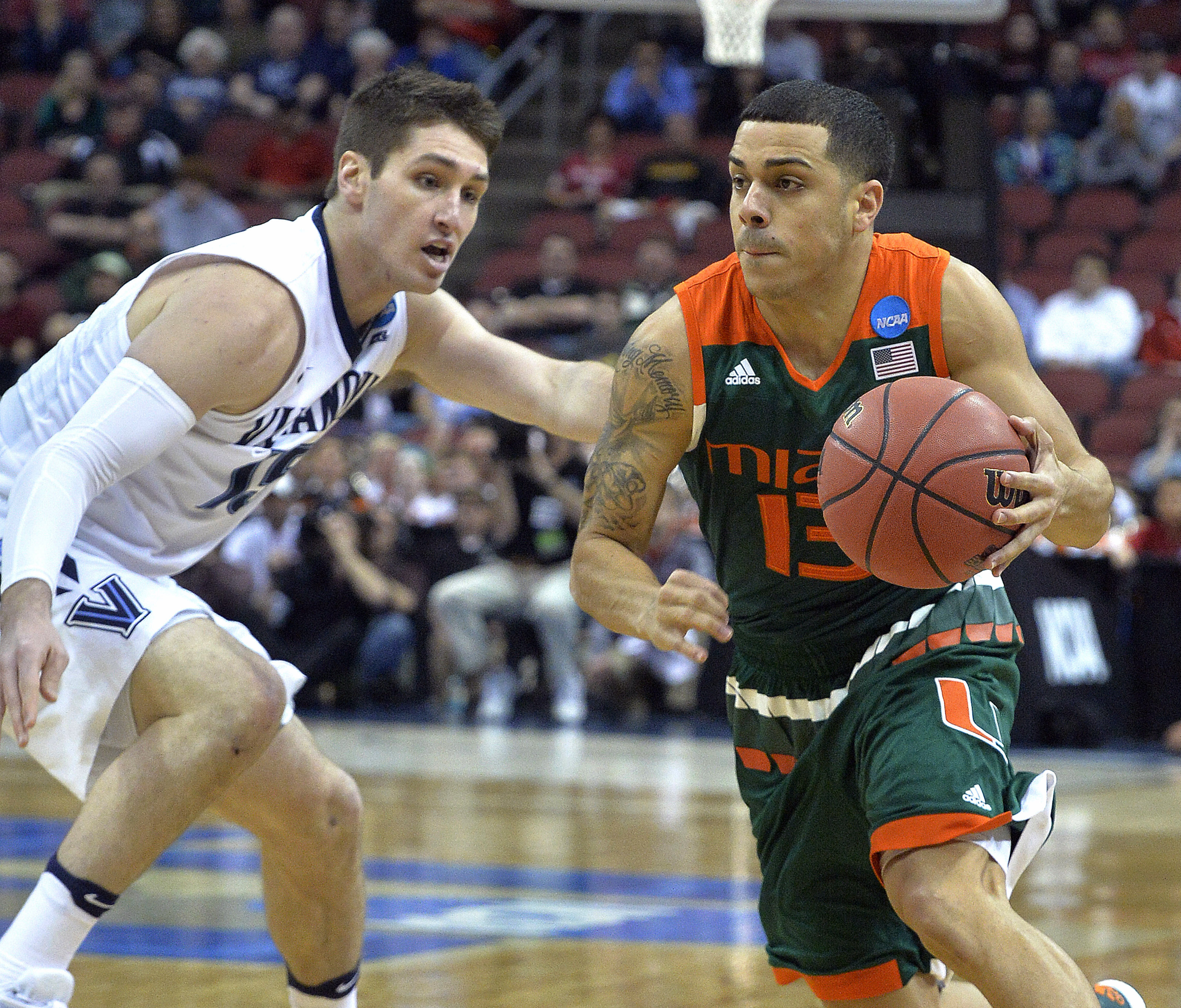 Miami guard Angel Rodriguez (13) drives around Villanova guard Ryan Arcidiacono (15) during the first half of an NCAA college basketball game in the regional semifinals of the men's NCAA Tournament in Louisville, Ky., Thursday, March 24, 2016. (AP Photo/T