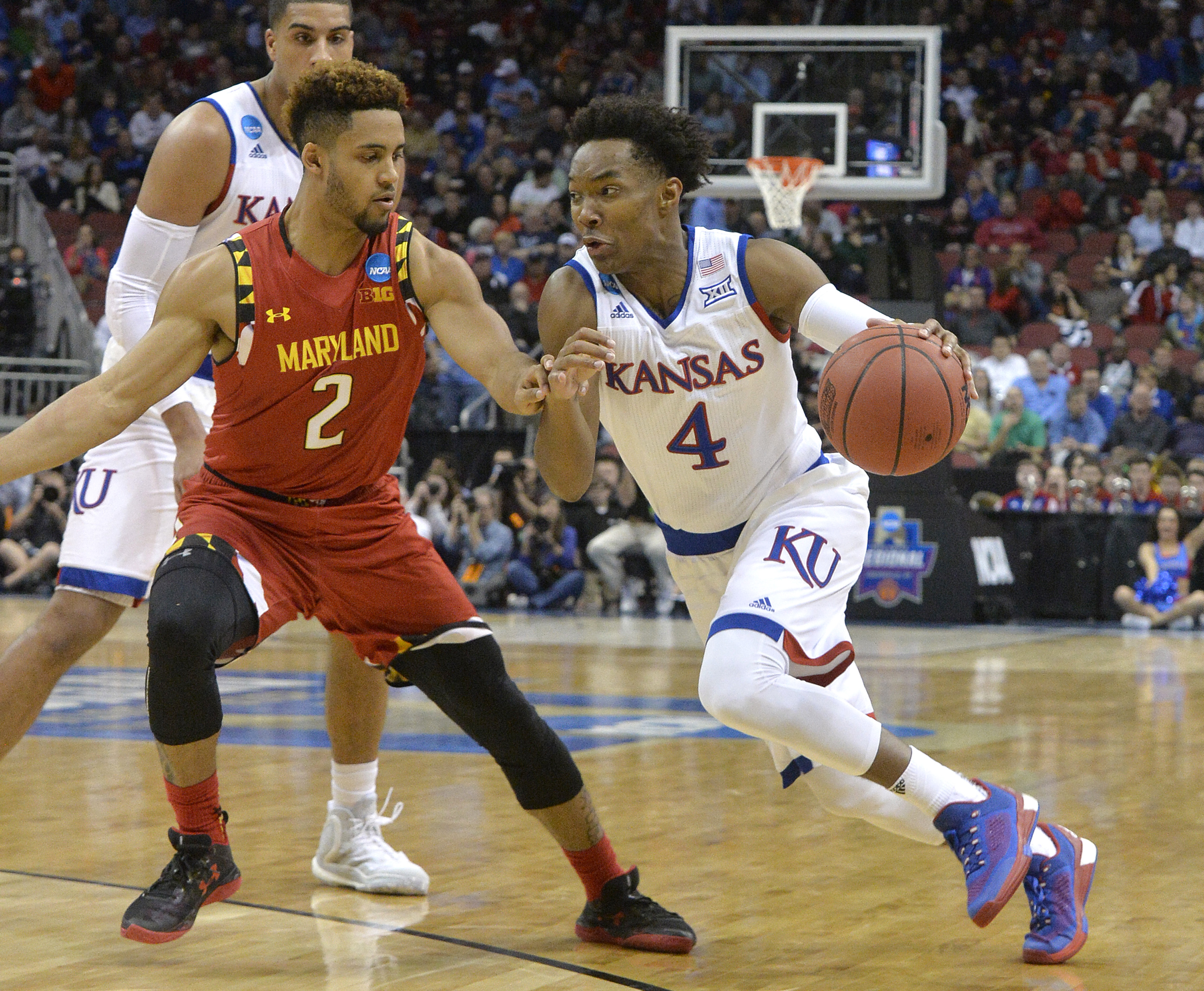 Kansas guard Devonte' Graham (4) drives against Maryland guard Melo Trimble (2) during the first half of an NCAA college basketball game in the regional semifinals of the men's NCAA Tournament in Louisville, Ky., Thursday, March 24, 2016. (AP Photo/Timoth