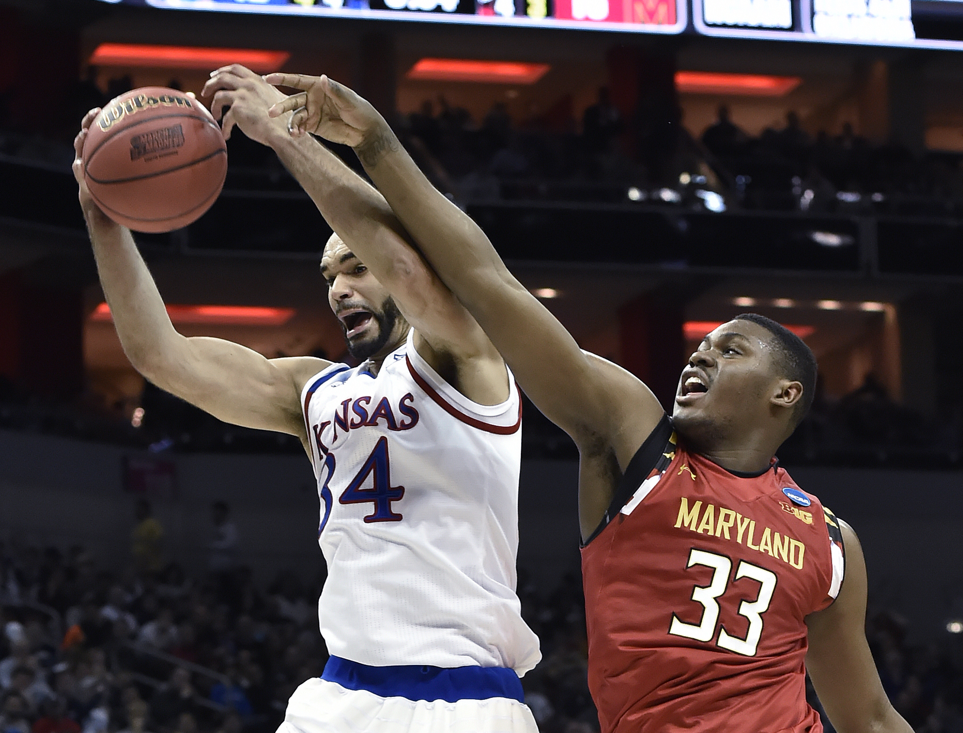 Kansas forward Perry Ellis (34) pulls down a rebound away from Maryland center Diamond Stone (33) during the first half of an NCAA college basketball game in the regional semifinals of the men's NCAA Tournament, in Louisville, Ky., Thursday, March 24, 201