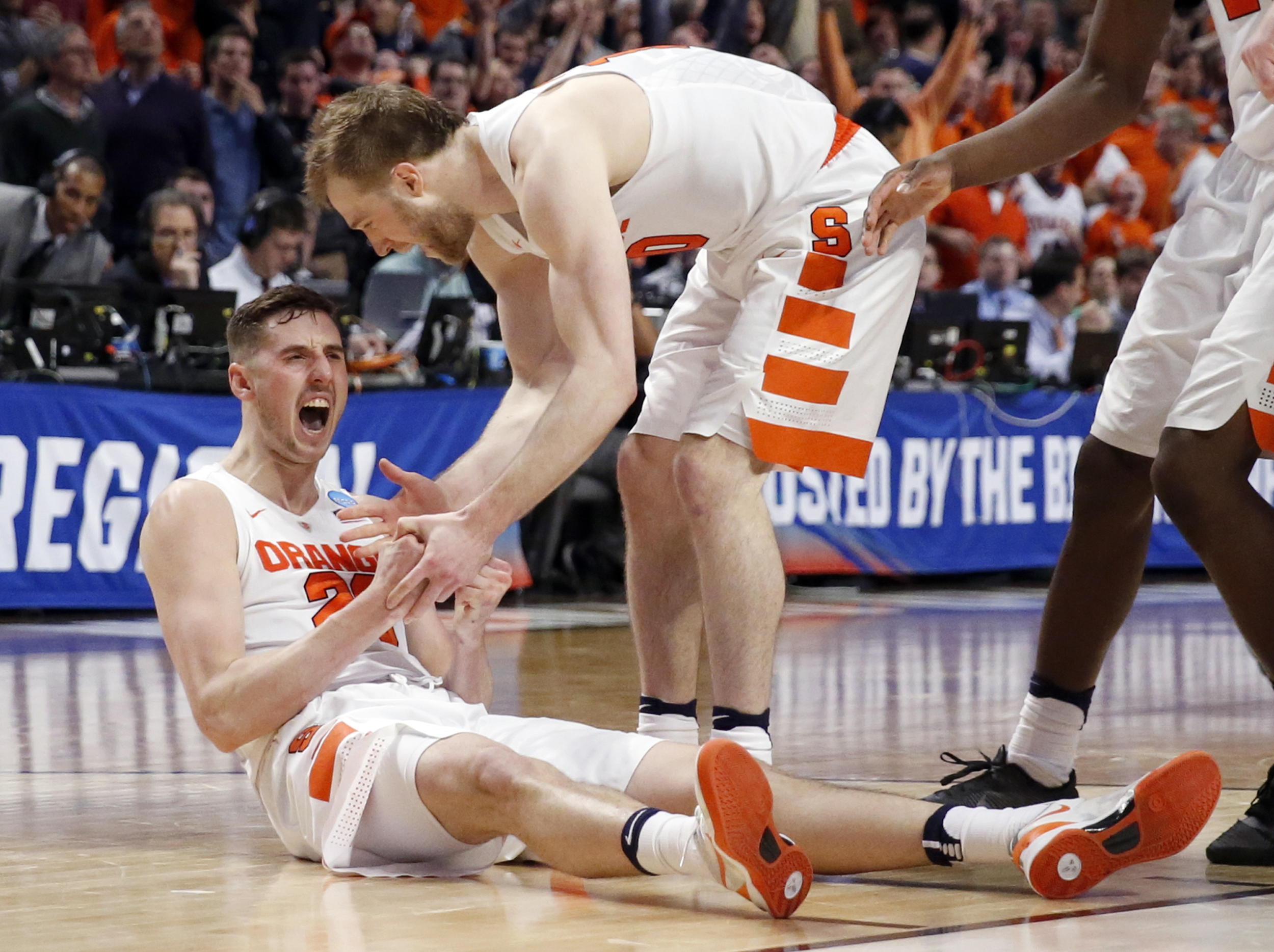 Syracuse's Tyler Lydon (20) celebrates with Trevor Cooney (10) after getting fouled in the final seconds of a college basketball game in the regional semifinals of the NCAA Tournament, Friday, March 25, 2016, in Chicago. Syracuse won 63-60. (AP Photo/Char