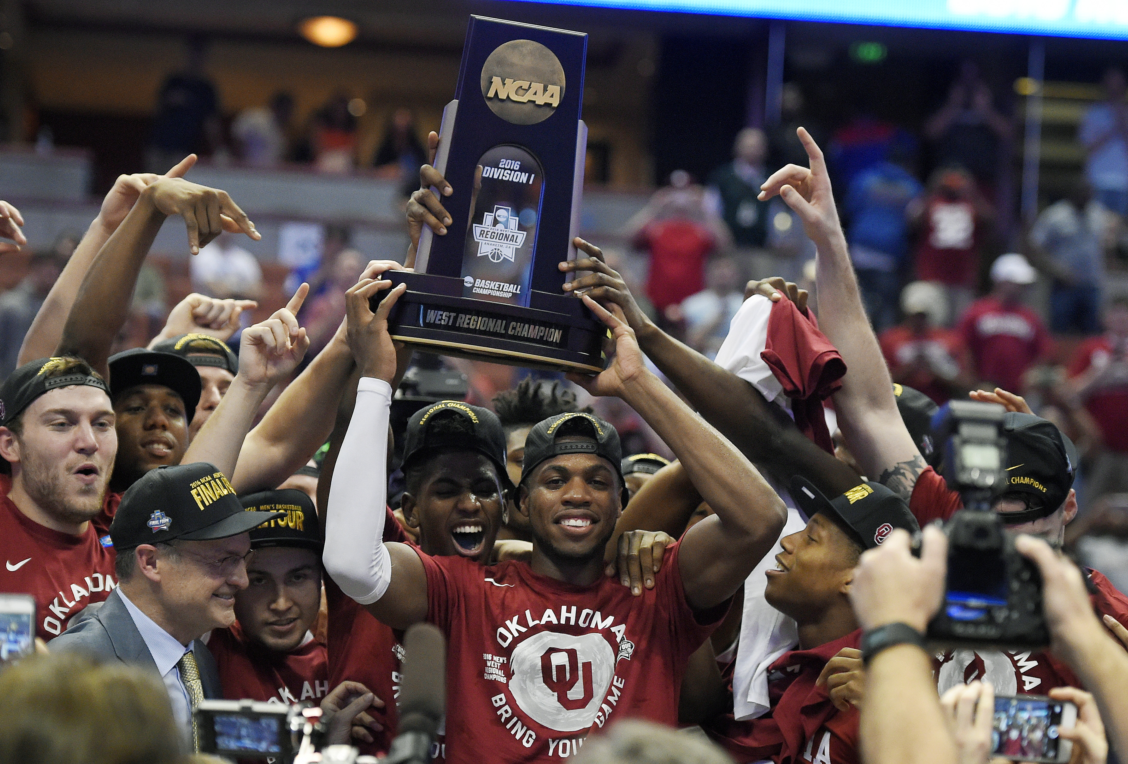 Oklahoma guard Buddy Hield, center, holds the trophy after their win against Oregon during an NCAA college basketball game in the regional finals of the NCAA Tournament, Saturday, March 26, 2016, in Anaheim, Calif.(AP Photo/Mark J. Terrill)