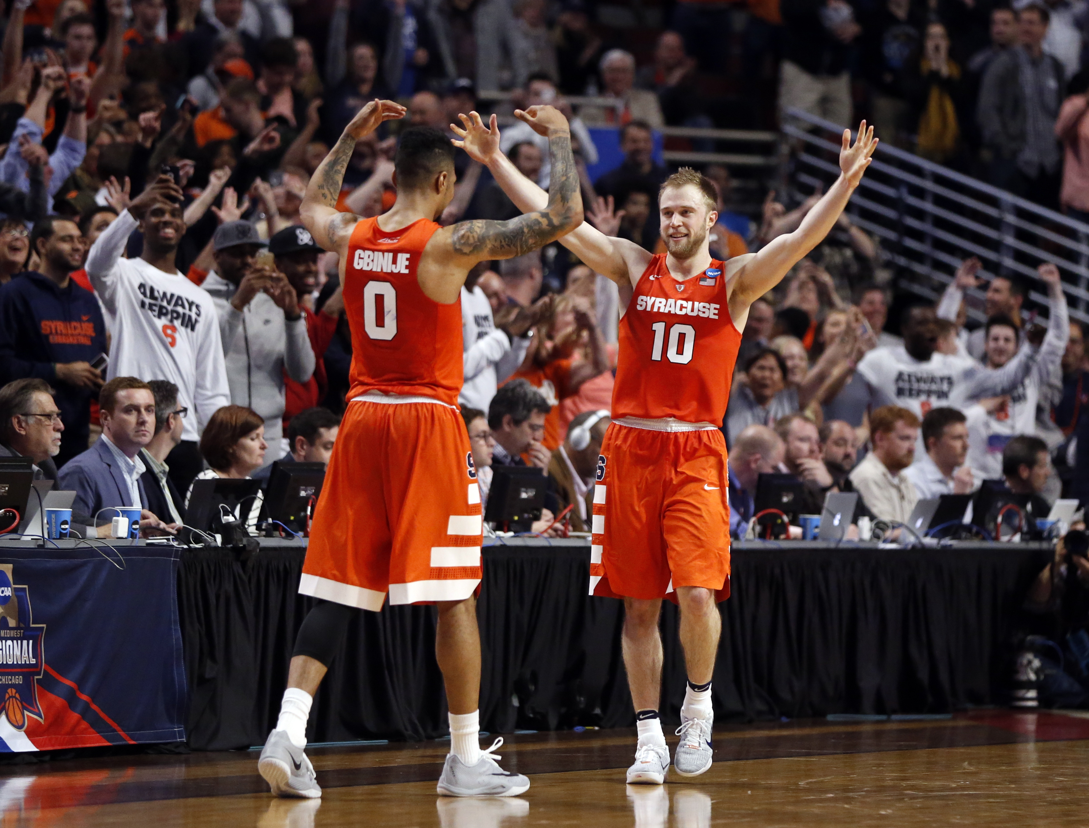 Syracuse's Michael Gbinije (0) and Trevor Cooney (10) celebrate after a college basketball game against Virginia in the regional finals of the NCAA Tournament, Sunday, March 27, 2016, in Chicago. Syracuse won 68-62. (AP Photo/Charles Rex Arbogast)
