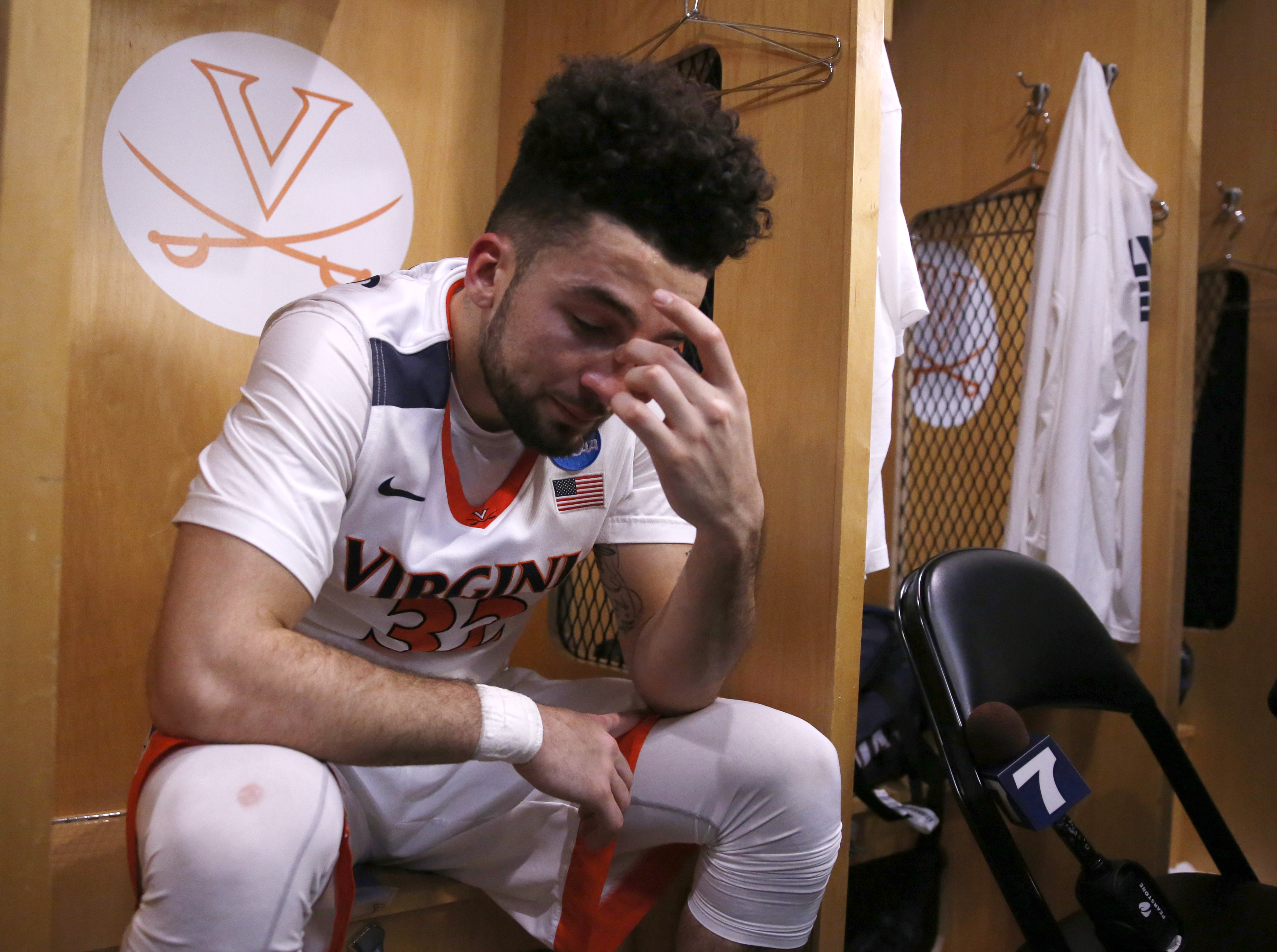 Virginia's London Perrantes (32) wipes his tears as he sits in the locker room after an NCAA college basketball game against Syracuse in the regional finals of the NCAA Tournament, Sunday, March 27, 2016, in Chicago. Syracuse won 68-62. (AP Photo/Charles