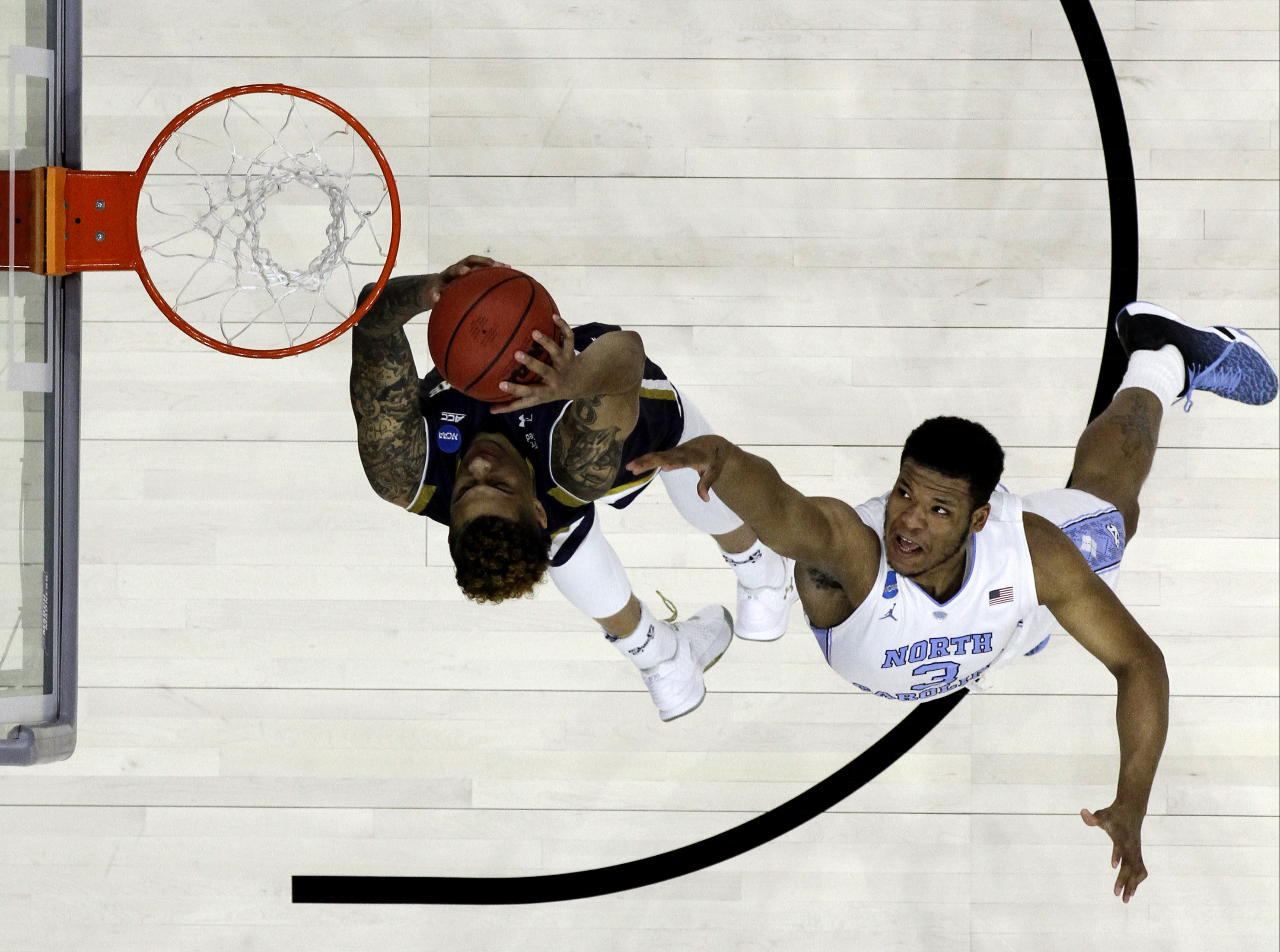 Notre Dame's Zach Auguste, left, goes up for a shot past North Carolina's Kennedy Meeks during the first half of a regional final men's college basketball game in the NCAA Tournament, Sunday, March 27, 2016, in Philadelphia. (AP Photo/Chris Szagola)