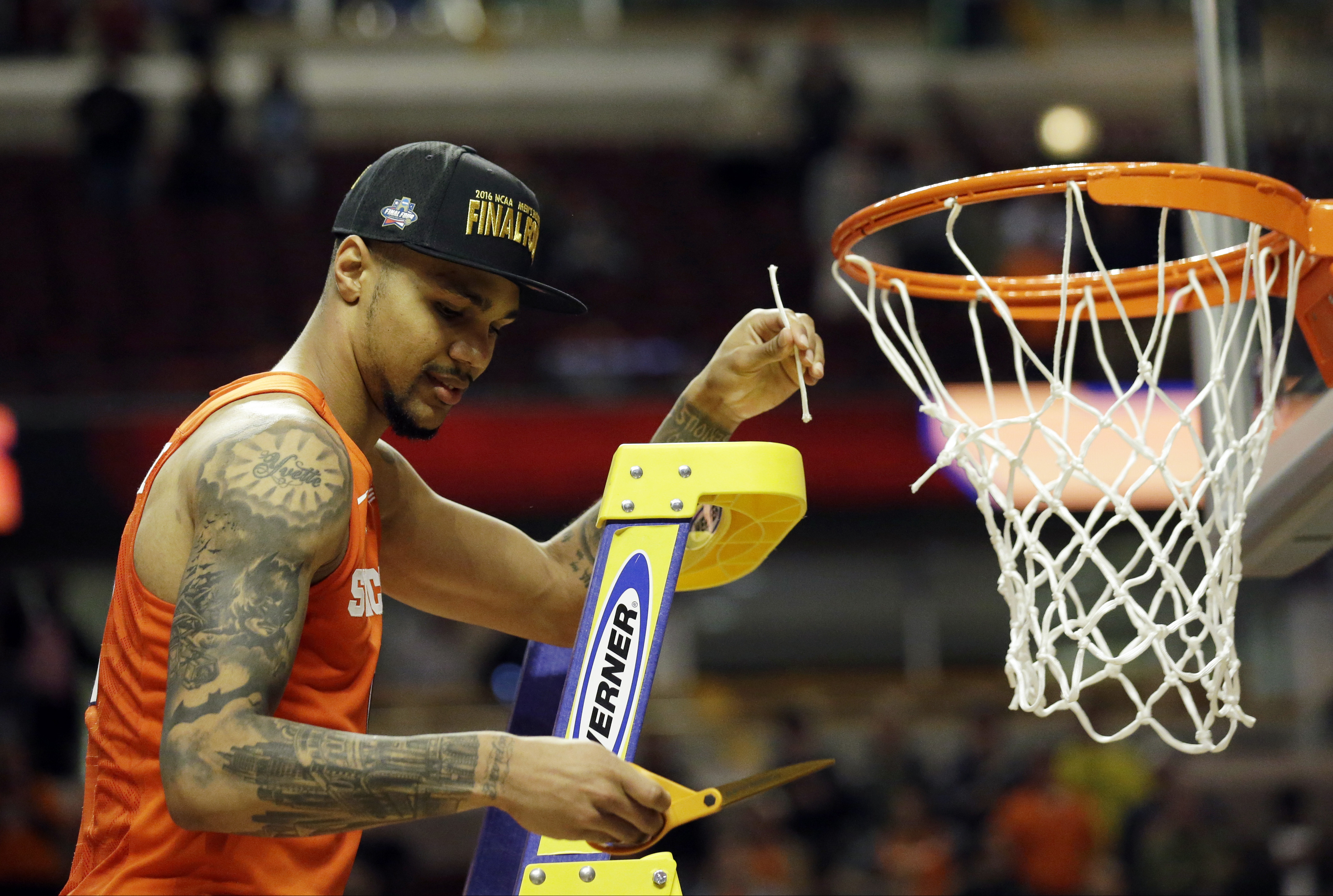 Syracuse's Michael Gbinije cuts down the net after their win against Virginia in an NCAA college basketball game in the regional finals of the NCAA Tournament, Sunday, March 27, 2016, in Chicago. Syracuse won 68-62. (AP Photo/Nam Y. Huh)