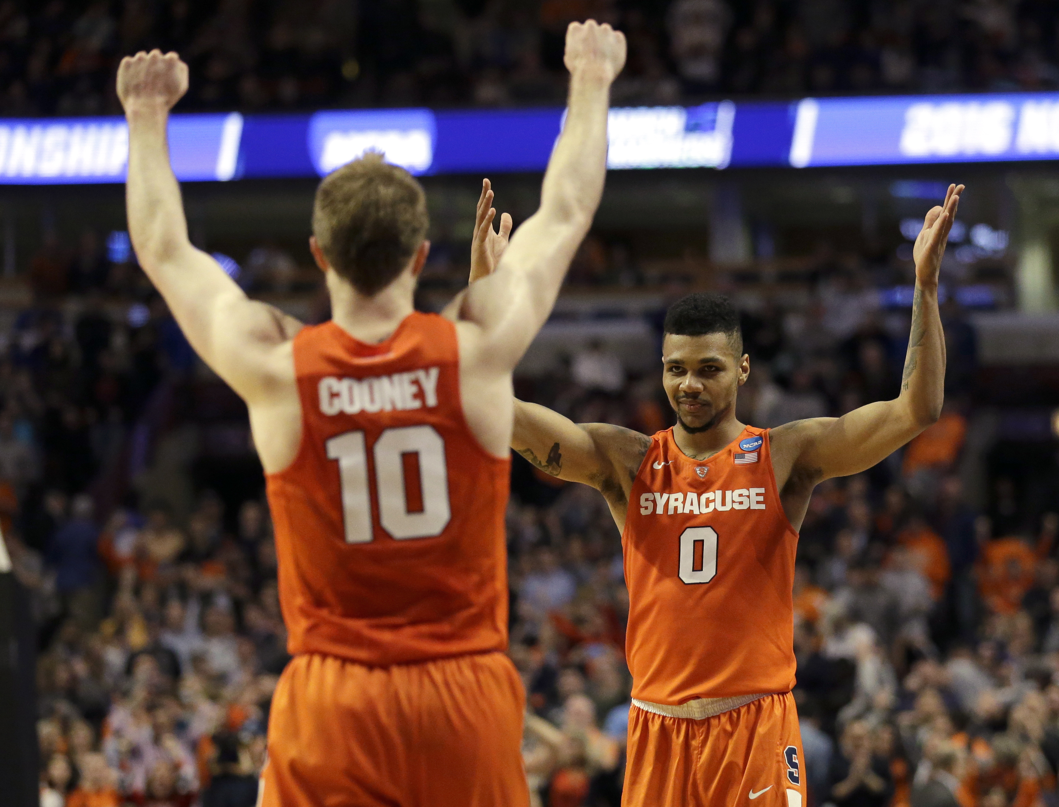 Syracuse's Trevor Cooney (10) and Michael Gbinije (0) celebrate in the closing seconds of a college basketball game against Virginia in the regional finals of the NCAA Tournament, Sunday, March 27, 2016, in Chicago. Syracuse won 68-62. (AP Photo/Nam Y. Hu