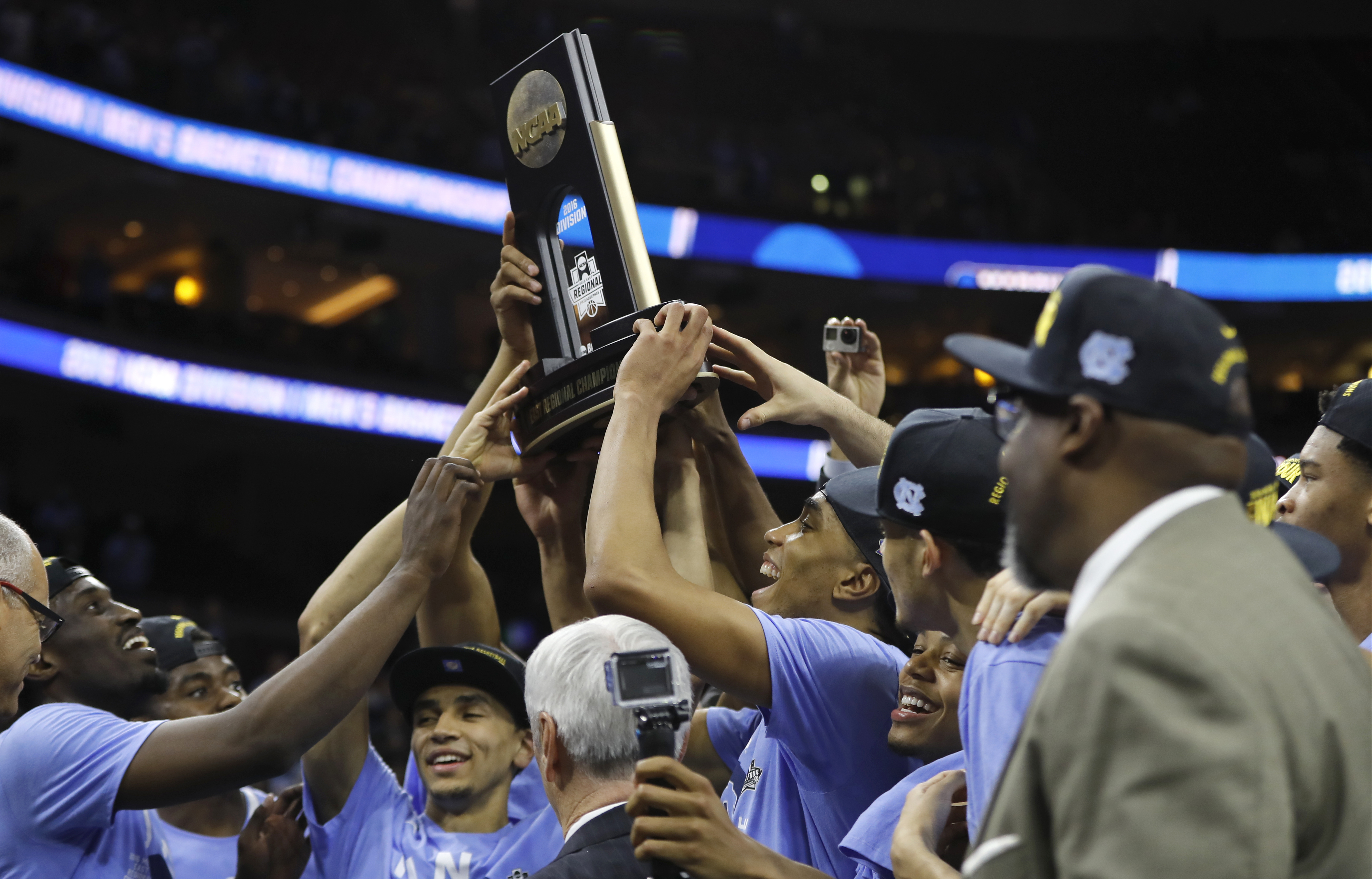 North Carolina players celebrate with the trophy after winning a regional final men's college basketball game against Notre Dame in the NCAA Tournament, Sunday, March 27, 2016, in Philadelphia. North Carolina won 88-74 to advance to the Final Four. (AP Ph