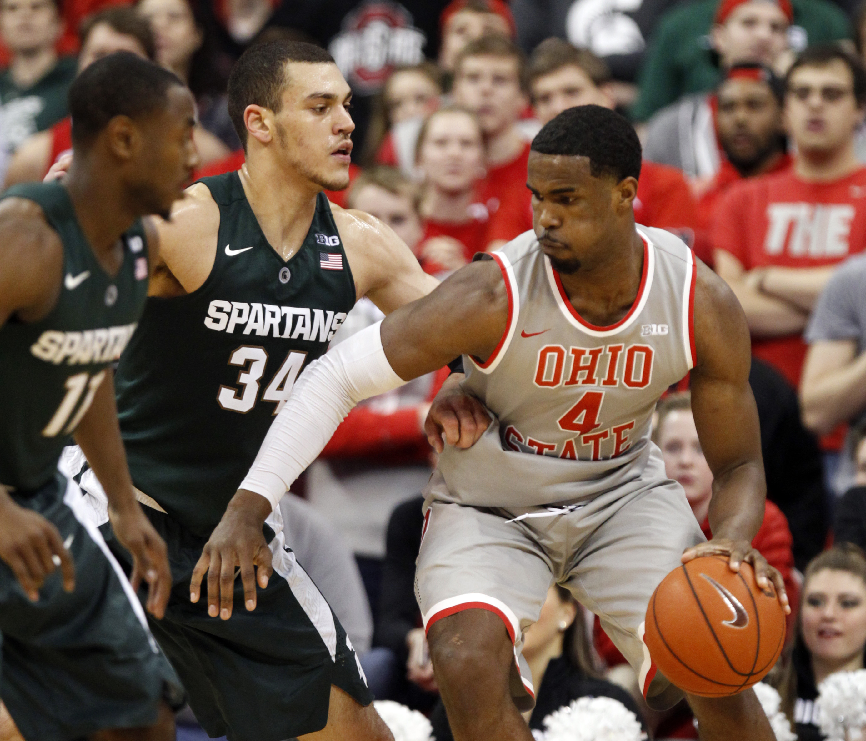 Ohio State's Daniel Giddens, right, works against Michigan State's Gavin Schilling, center, and Lourawls Nairn Jr. during an NCAA college basketball game in Columbus, Ohio, Wednesday, Feb. 23, 2016. Michigan State won 81-62. (AP Photo/Paul Vernon)