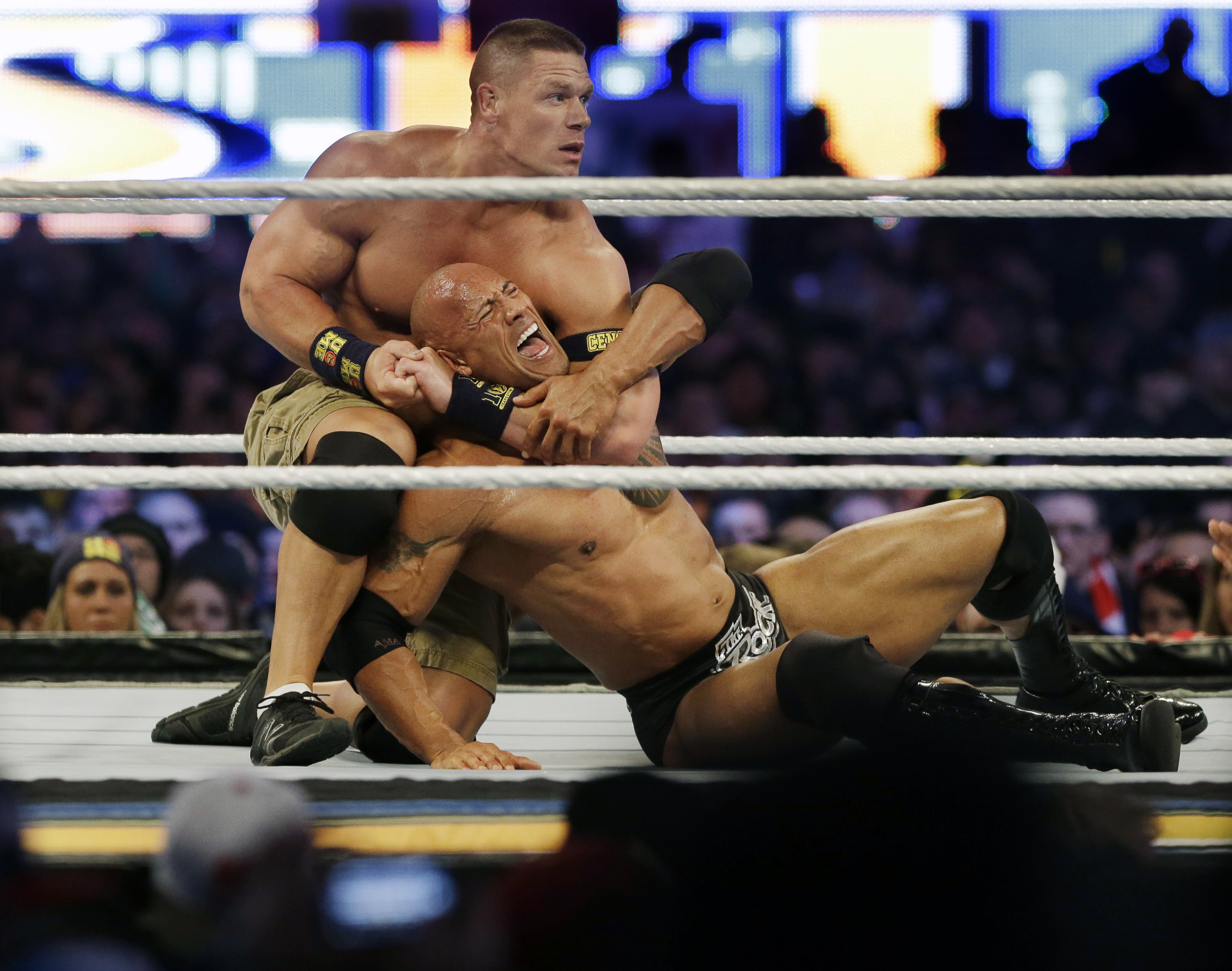 FILE -In a Sunday, April 7, 2013 file photo, wrestler John Cena, top, chokes Dwayne Douglas Johnson, known as The Rock as they wrestle during Wrestlemania, in East Rutherford, N.J. WWE bills WrestleMania as its Super Bowl, and is headed to a stadium worth