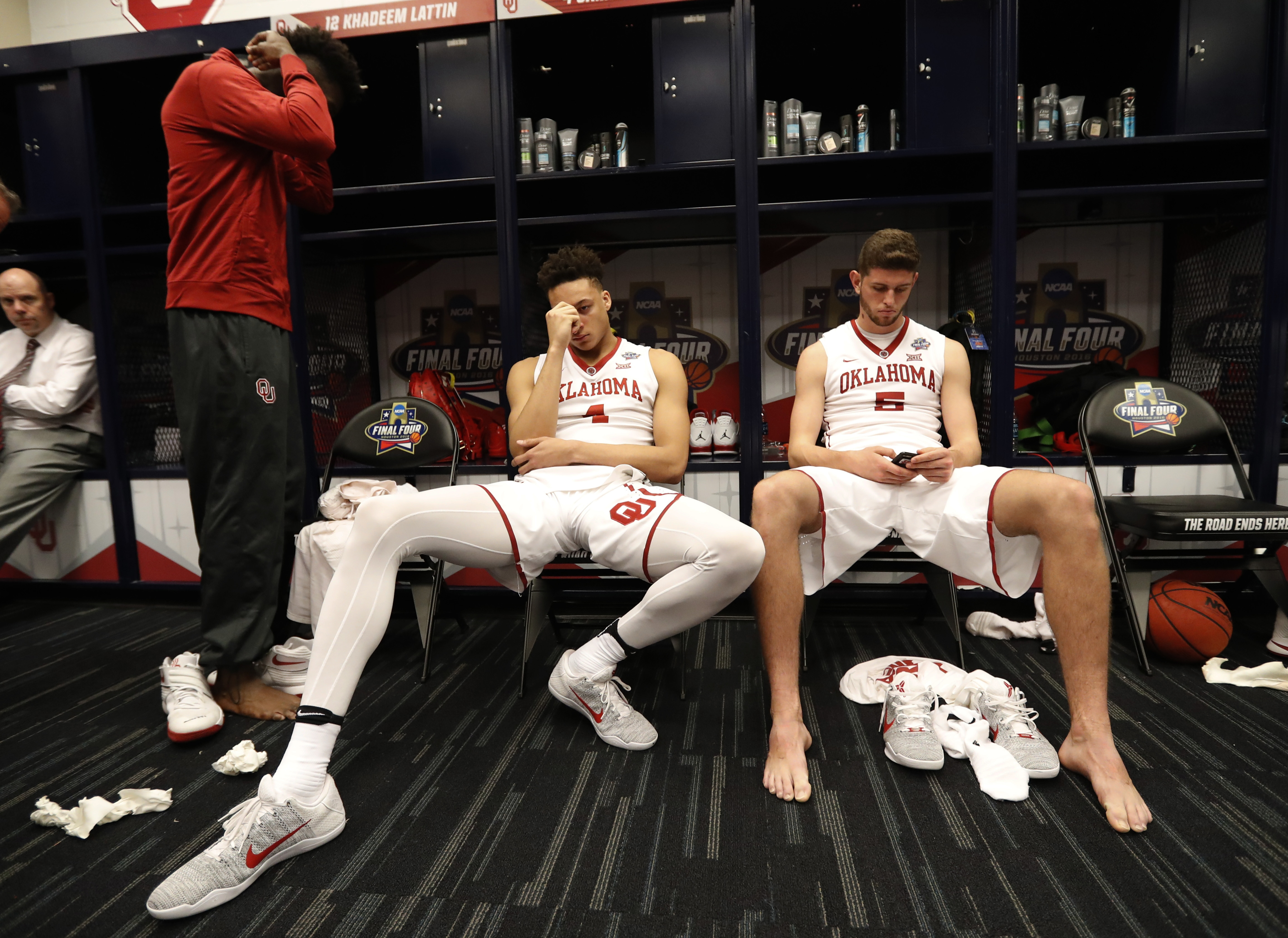 Oklahoma's Jamuni McNeace (4) and Matt Freeman (5) sit in the locker room after the NCAA Final Four tournament college basketball semifinal game against Villanova, Saturday, April 2, 2016, in Houston. Villanova won 95-51. (AP Photo/Eric Gay)