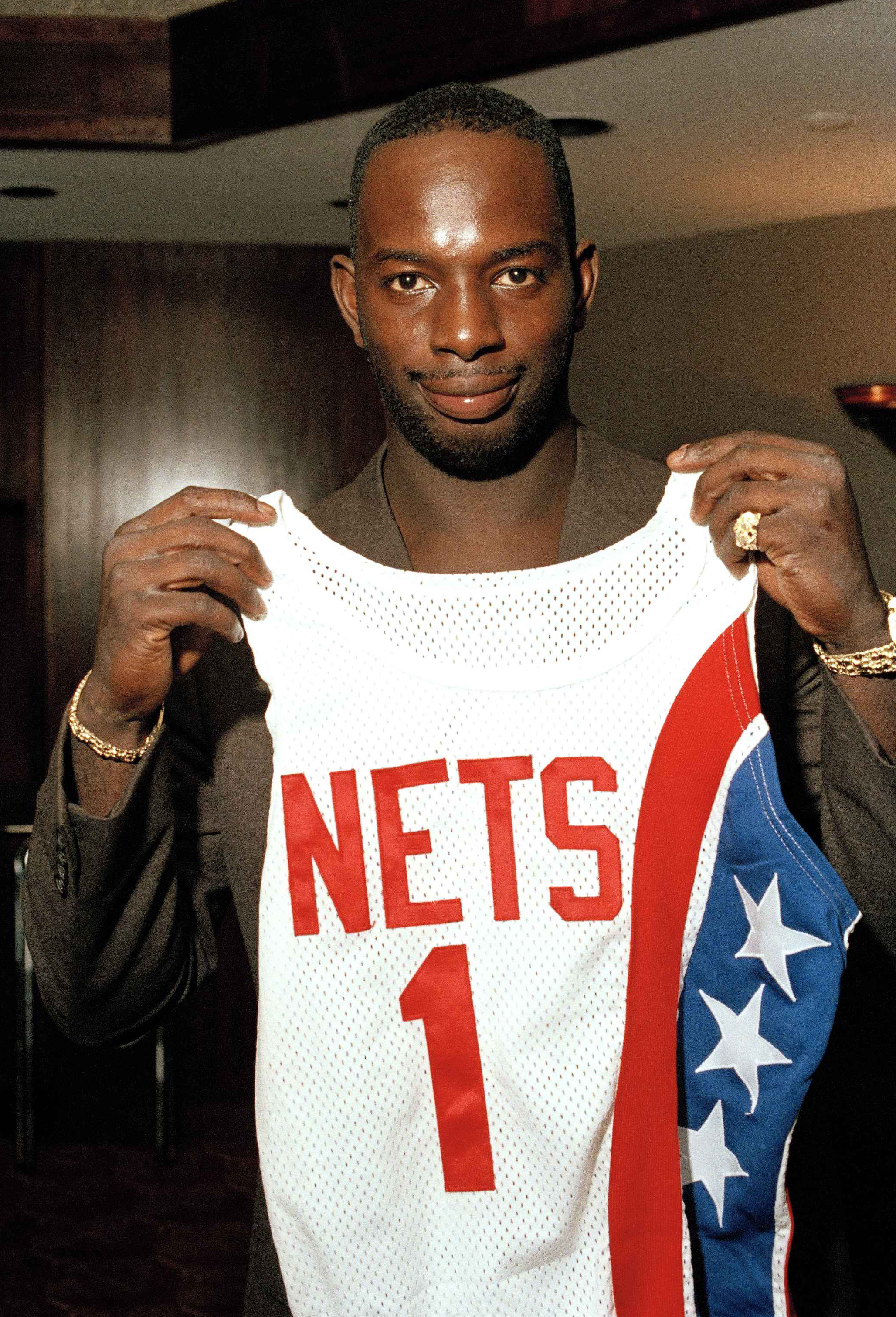 """FILE - In this Aug. 20, 1986 file photo, Dwayne """"Pearl"""" Washington, the first draft pick by the New Jersey Nets, holds up his new uniform during a press luncheon at the Meadowlands Arena in East Rutherford, N.J.  Washington, who went from New York City pl"""