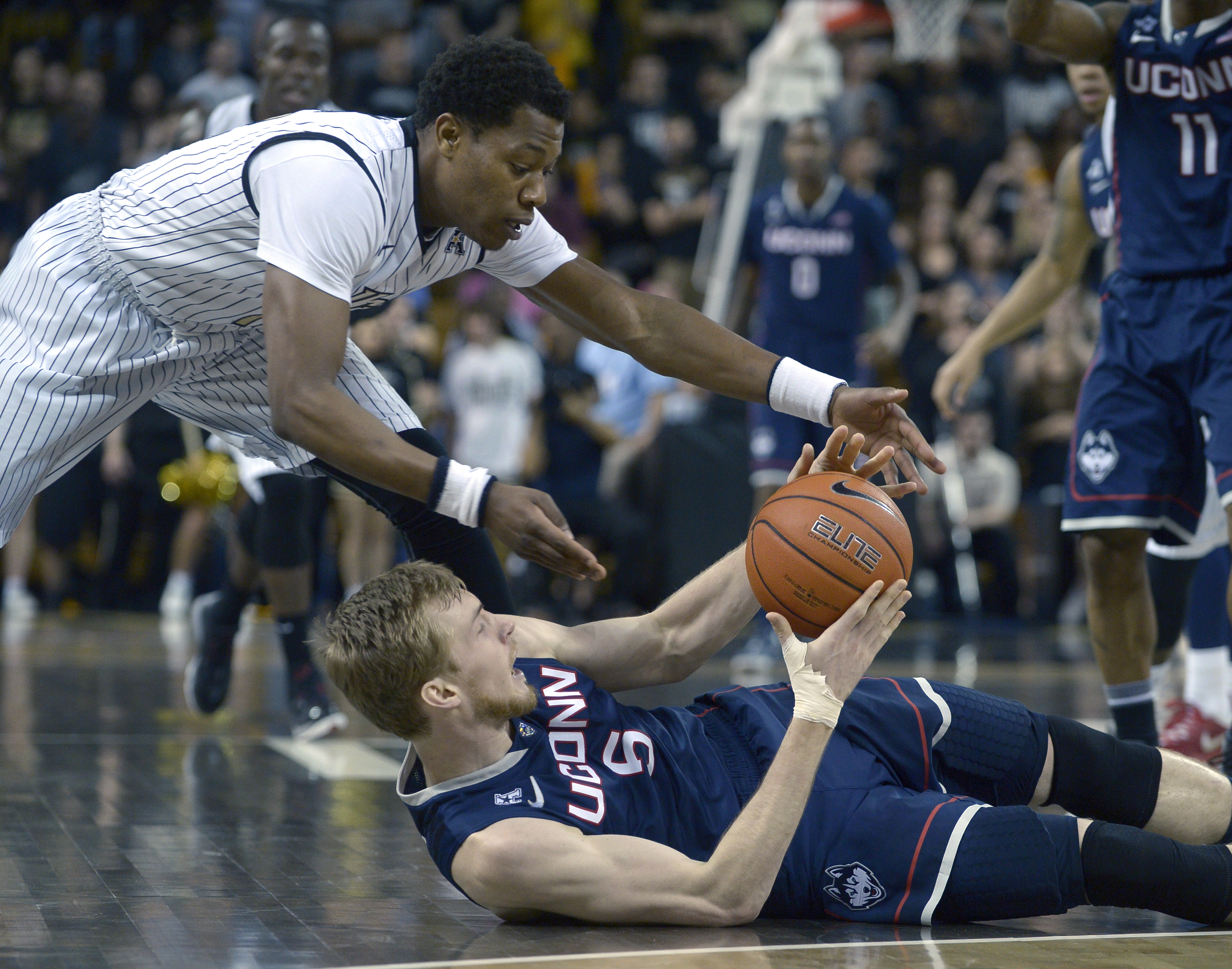 Central Florida guard Matt Williams, left, and Connecticut's Niels Giffey (5) battle for a loose ball during the first half of an NCAA college basketball game in Orlando, Fla., Sunday, Feb. 9, 2014.(AP Photo/Phelan M. Ebenhack)